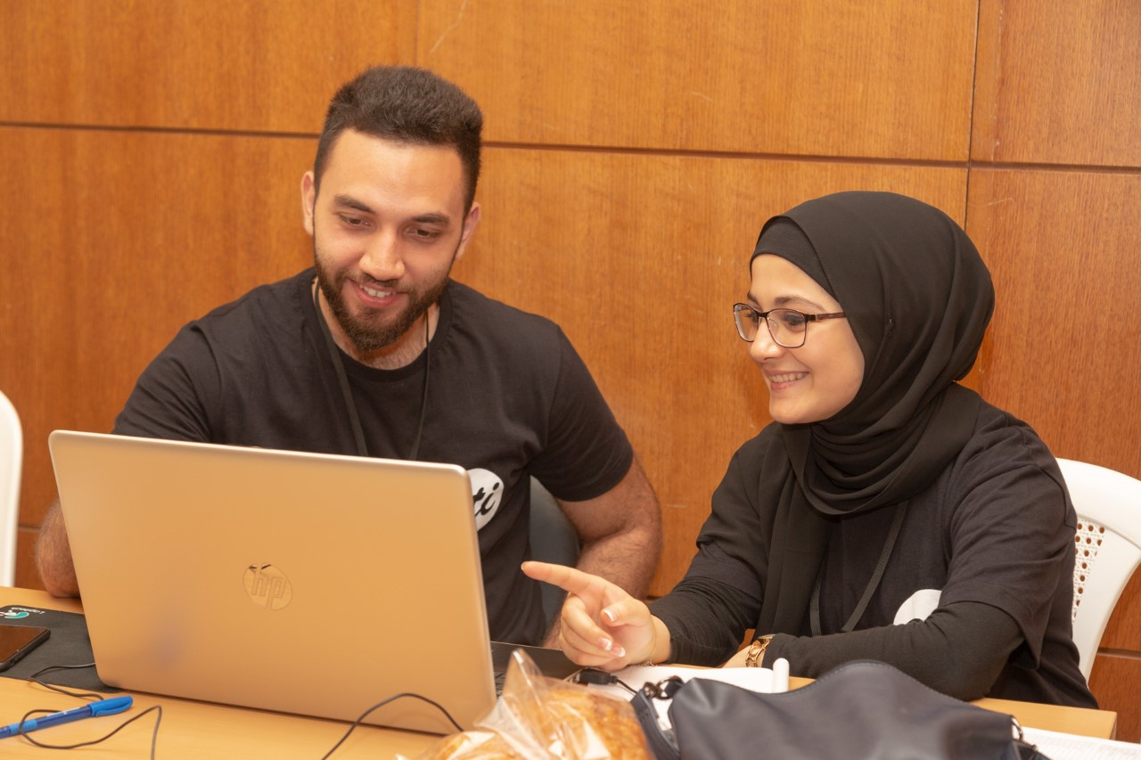 "A man and a woman sit at a light brown table, both staring at the screen of a silver laptop. Both are wearing black t-shirts with the ETI logo in the upper-left corner. The logo is a solid white circle with the letters ""ETI"" in black cursive text."