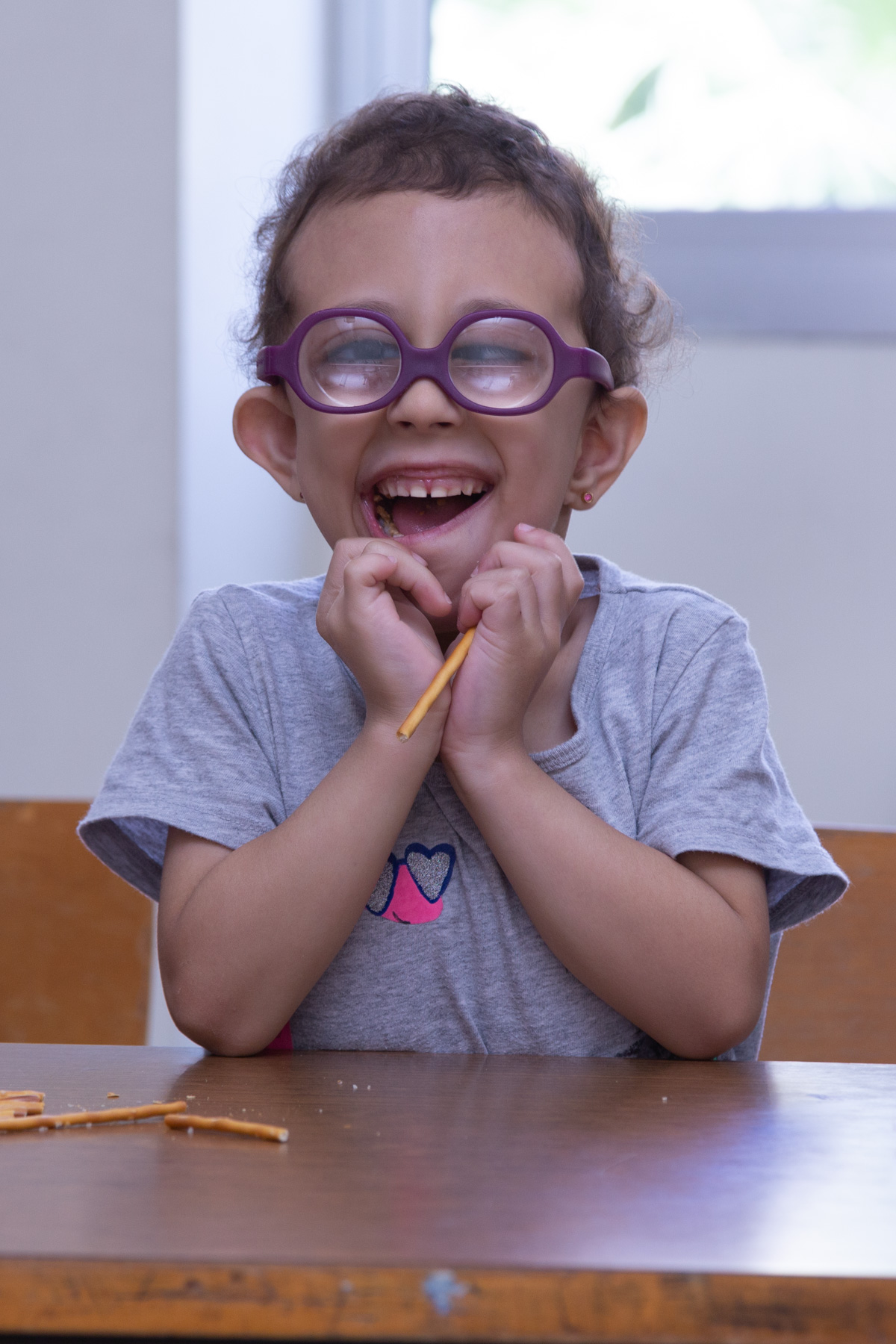 A child in bright purple eyeglasses smiles enthusiastically at the camera with their chin on their hands. The child is sitting at a wooden table with some pretzel sticks in front of them.