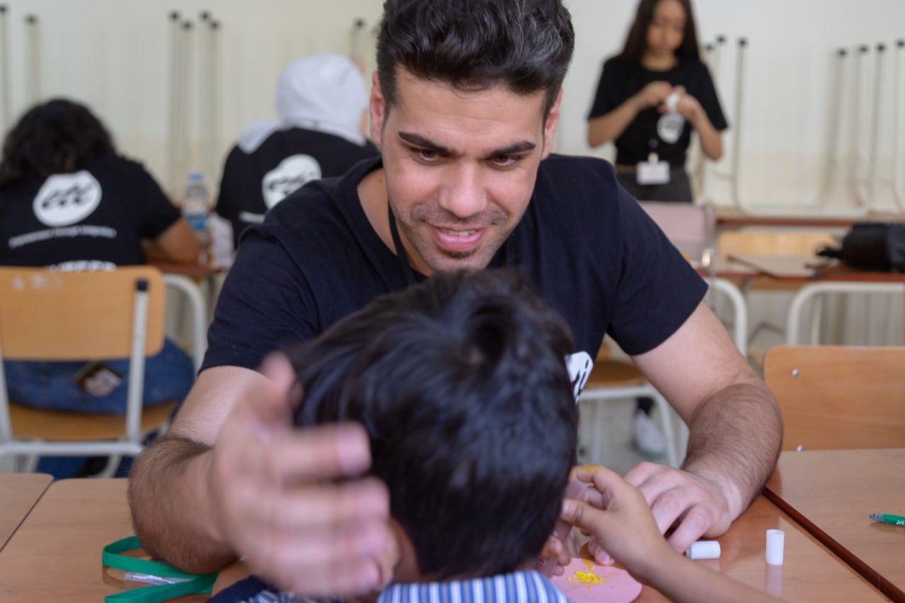 A man in a black t-shirt faces the camera. A young boy sits facing him at a small table. The man facing the camera reaches out to cup the side of the young boy's face.