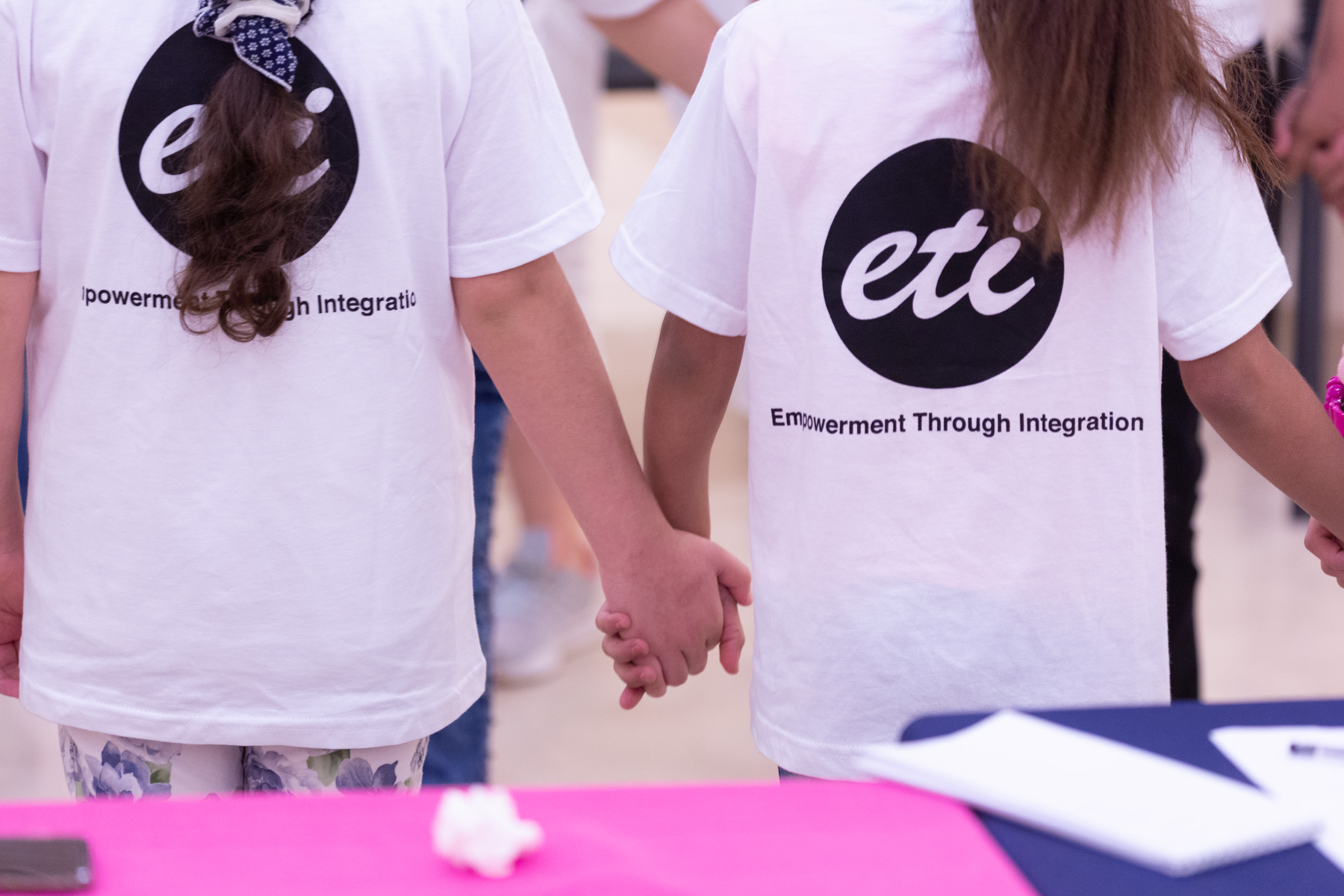 "We see the backs of two girls holding hands. Each girl wears her hair in a ponytail. Each is wearing a white t-shirt with the a solid black circle and the letters ""ETI"" in white cursive in the middle. Below this are the worlds ""Empowerment Through Integration"""