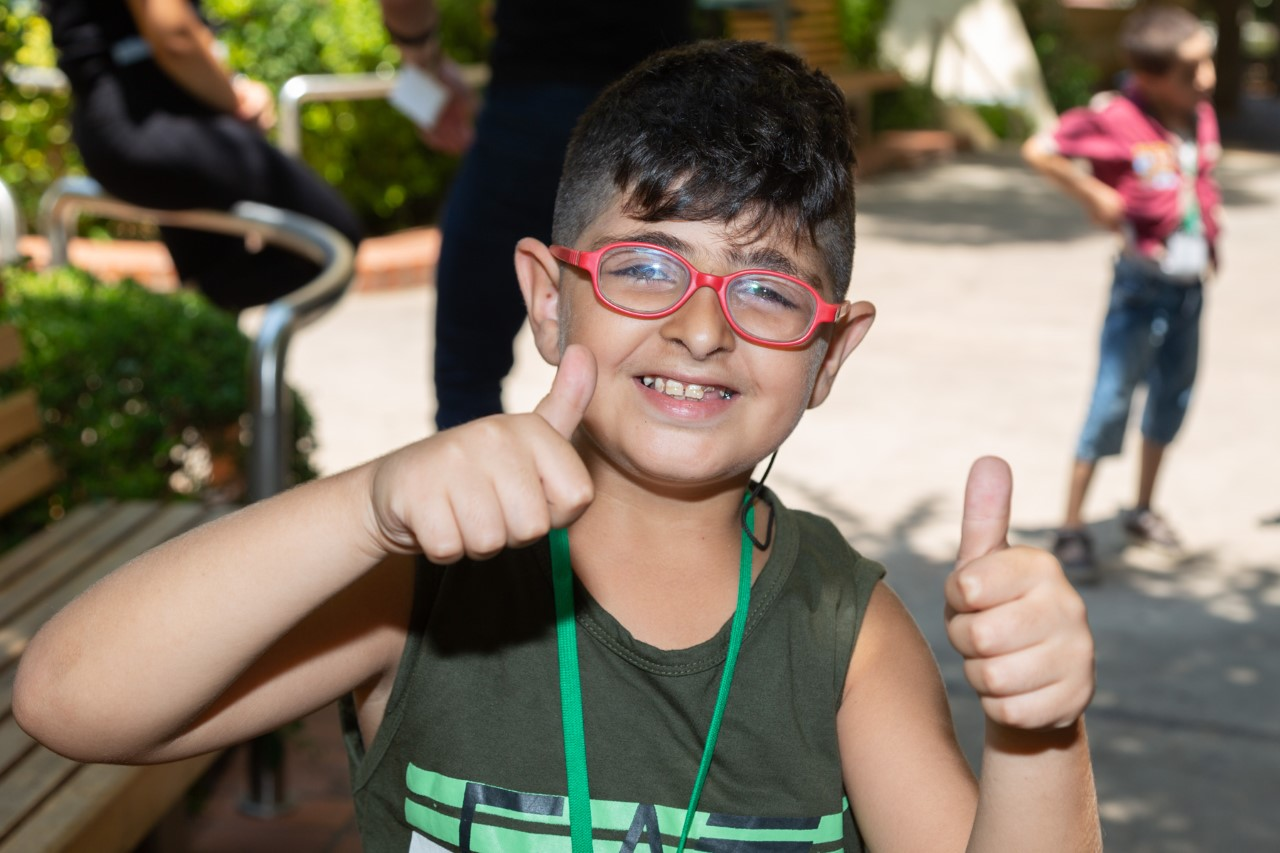 A boy with red glasses holds two thumbs up. He has black hair and is wearing a green tank top.
