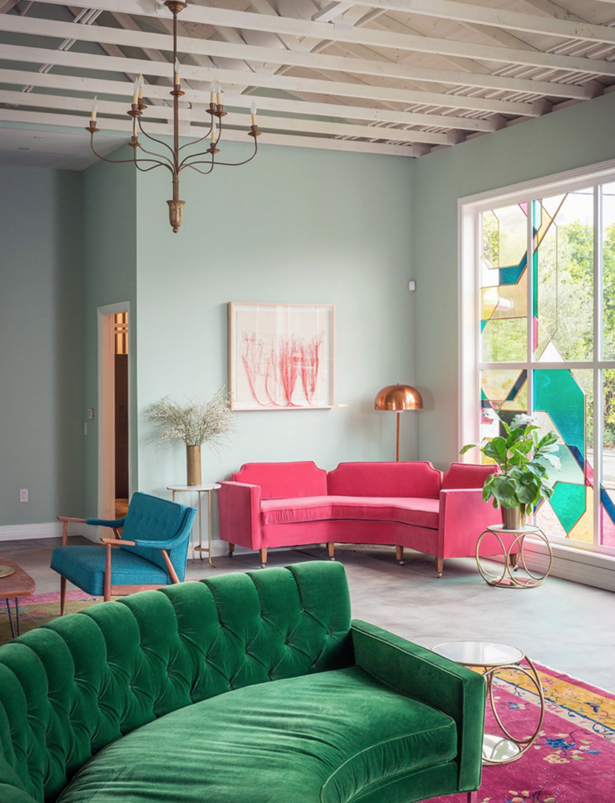Those bright velvet sofas and that huge stained glass window. I mean, does it get any prettier??Image via  Style by Emily Henderson .
