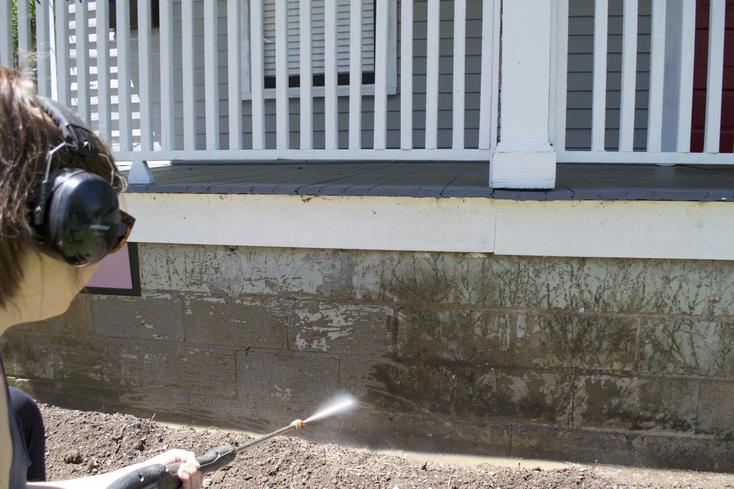 Pressure washing the foundation to prep for painting.