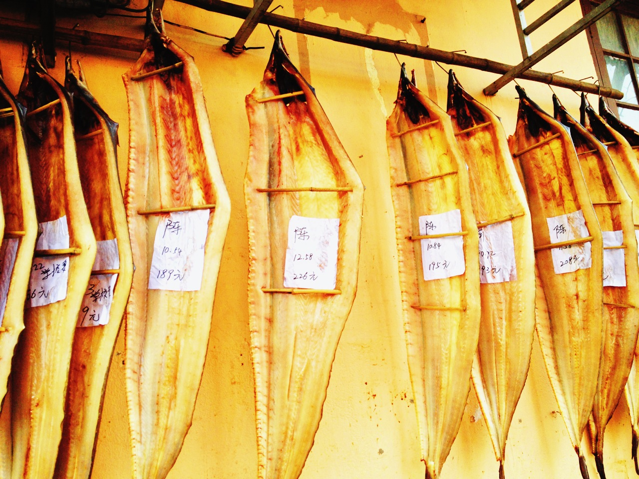 Dry-cured fish hanged alongthe street
