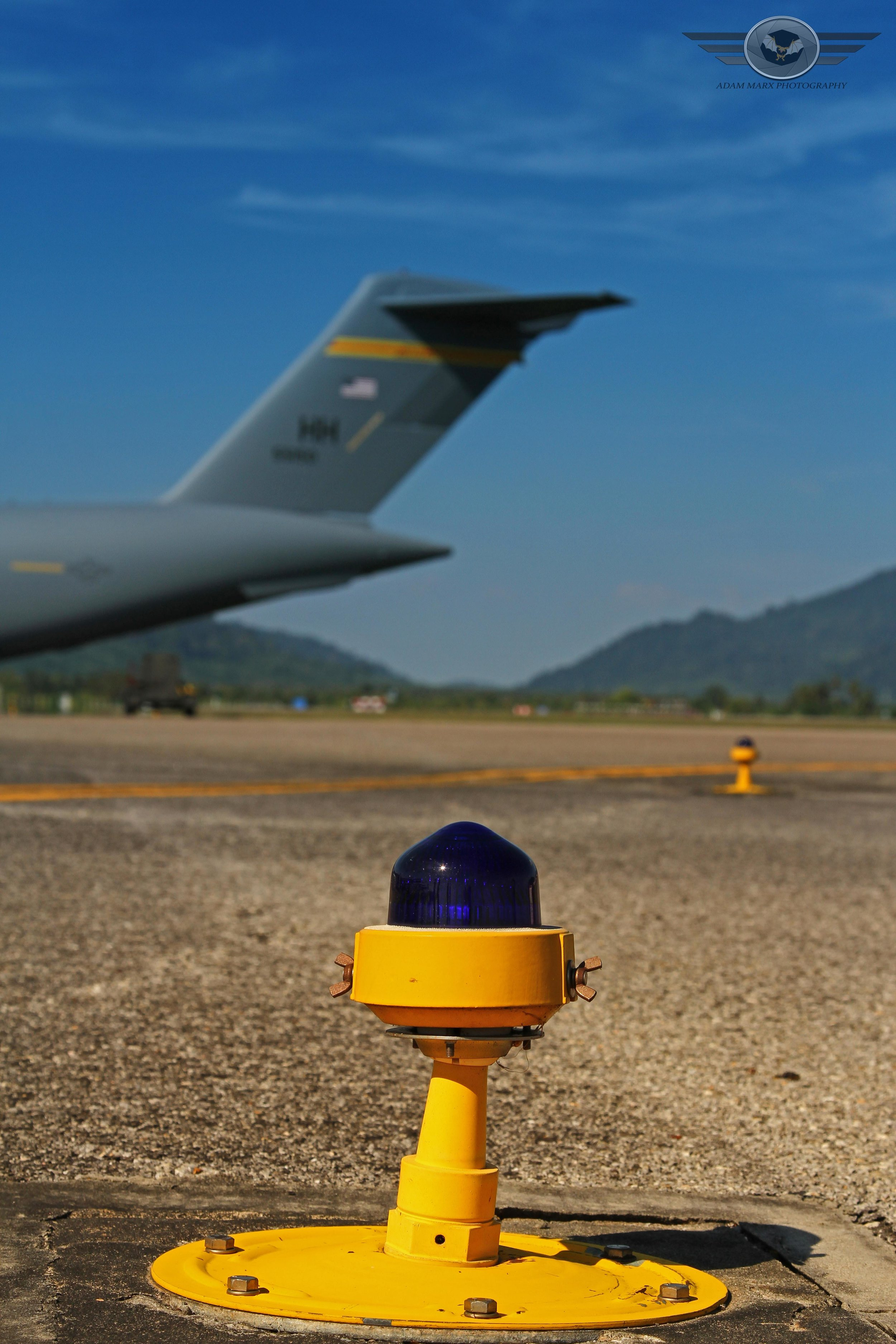 A creative shot in the foreground a taxilighty and in the background a tail of an C-17 from Hawaii.