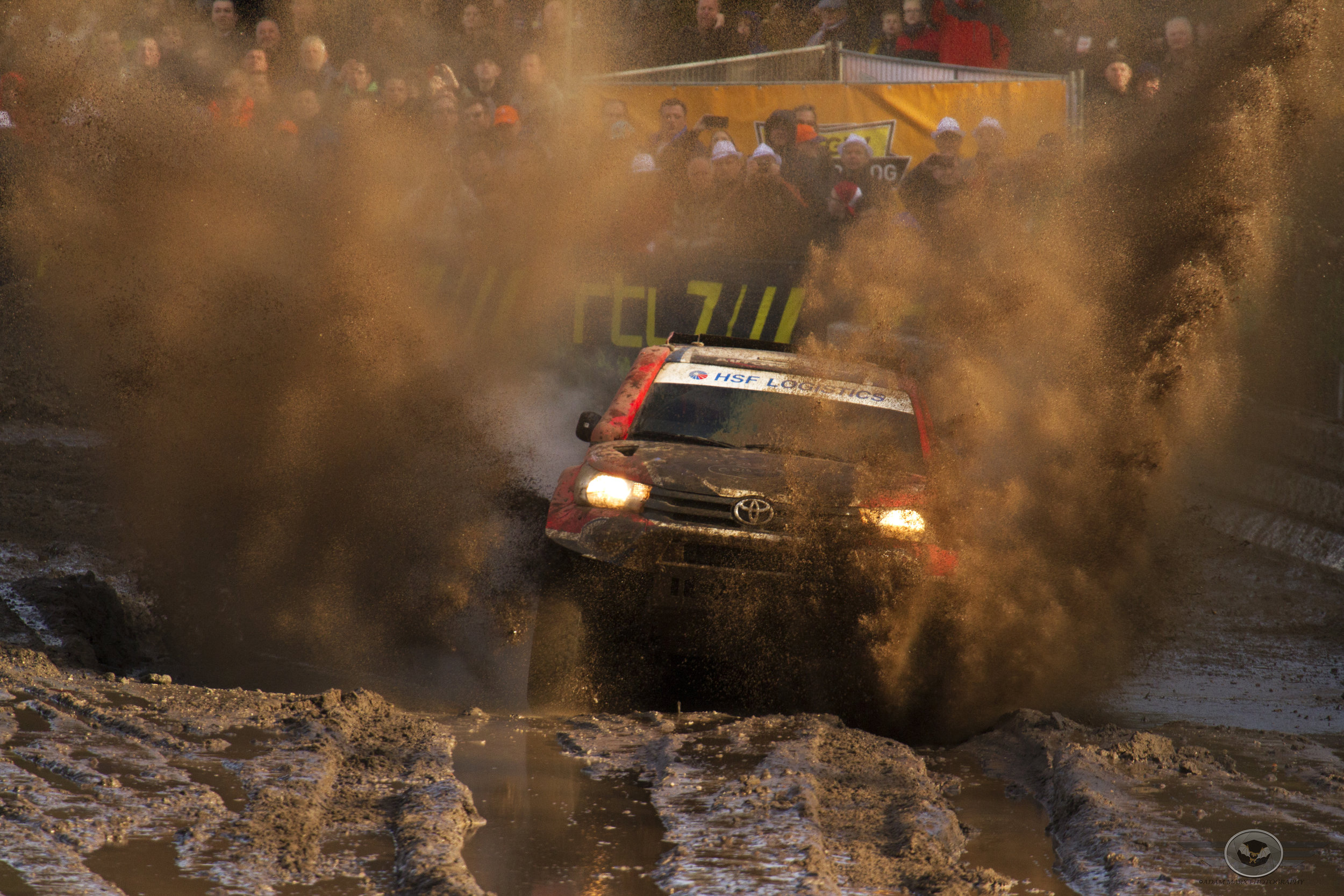 Mud explodes in front of the Toyota Hilux of Bernhard ten Brinke.