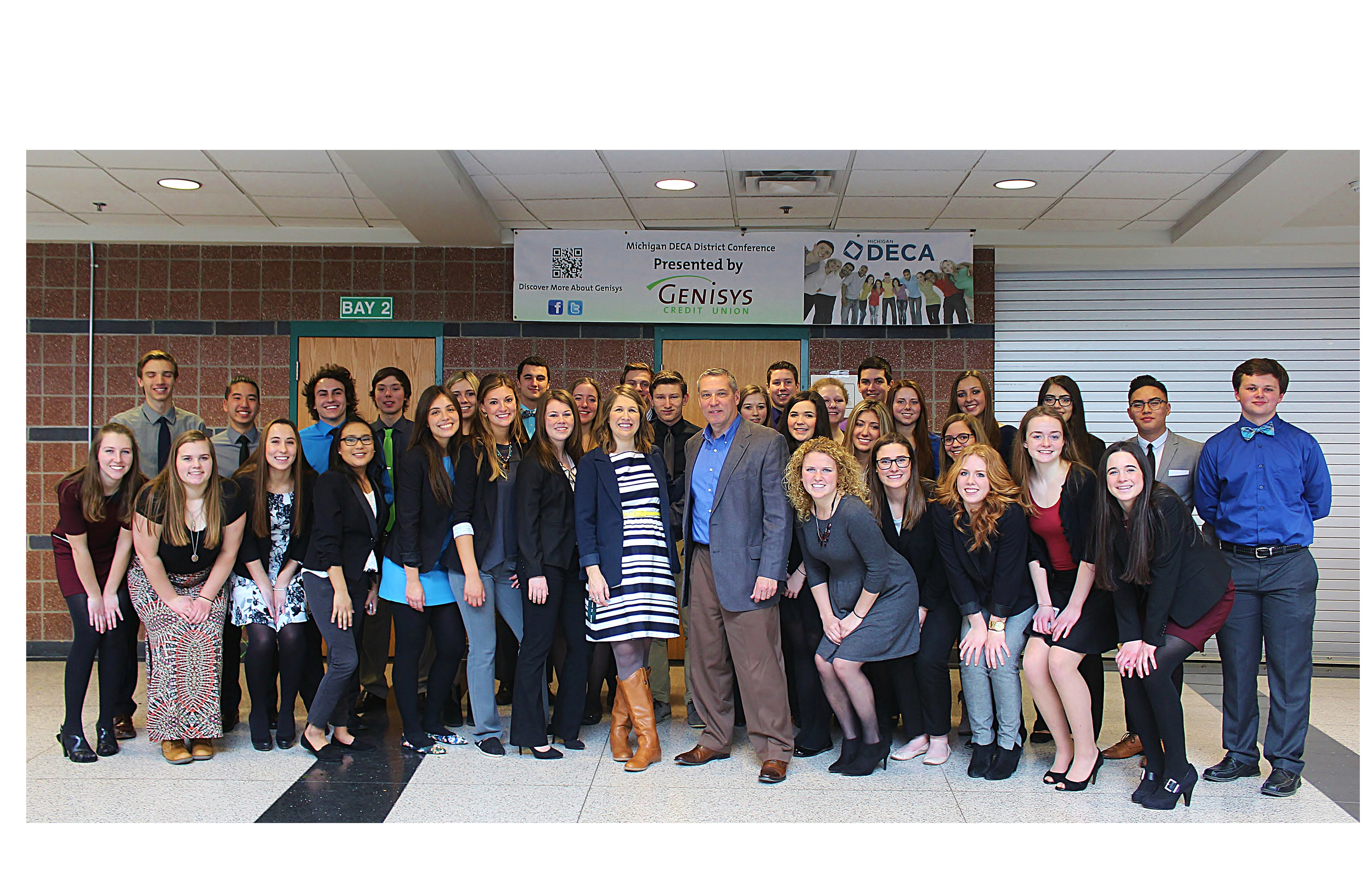 Above: Custom Threads & Sports, a long time local supplier of Lake Orion-branded apparel to school athletic programs and the community, recently provided a grant to the Lake Orion High School DECA team of students interested in sales and marketing careers. According to Custom Threads' President Mark McCord, the donation was made in recognition of the successful partnership between his business and the school district to provide goods for the high school's student run store and Lake Orion's web based spirit wear outlet.  Pictured, DECA Advisor Julia Dalrymple and Mark McCord, along with the students who competed in the recent DECA regional competition at Lake Orion High School. Photo Credit: Joe St. Henry.