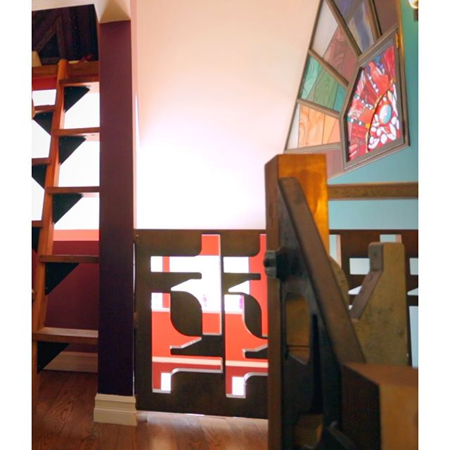 Mesmerizing shapes and colors add so much visual appeal to this small #ADU home.✨ Watch the tour—link in bio.✨ What you see here is the 2nd floor landing with a railing made from salvaged remnant steel—cut outs from machine parts. 🌈The stained glass window provides light and privacy for the bedroom. And on the right is alternating tread stairs to the storage loft. A great compact, sturdy alternative to a ladder.