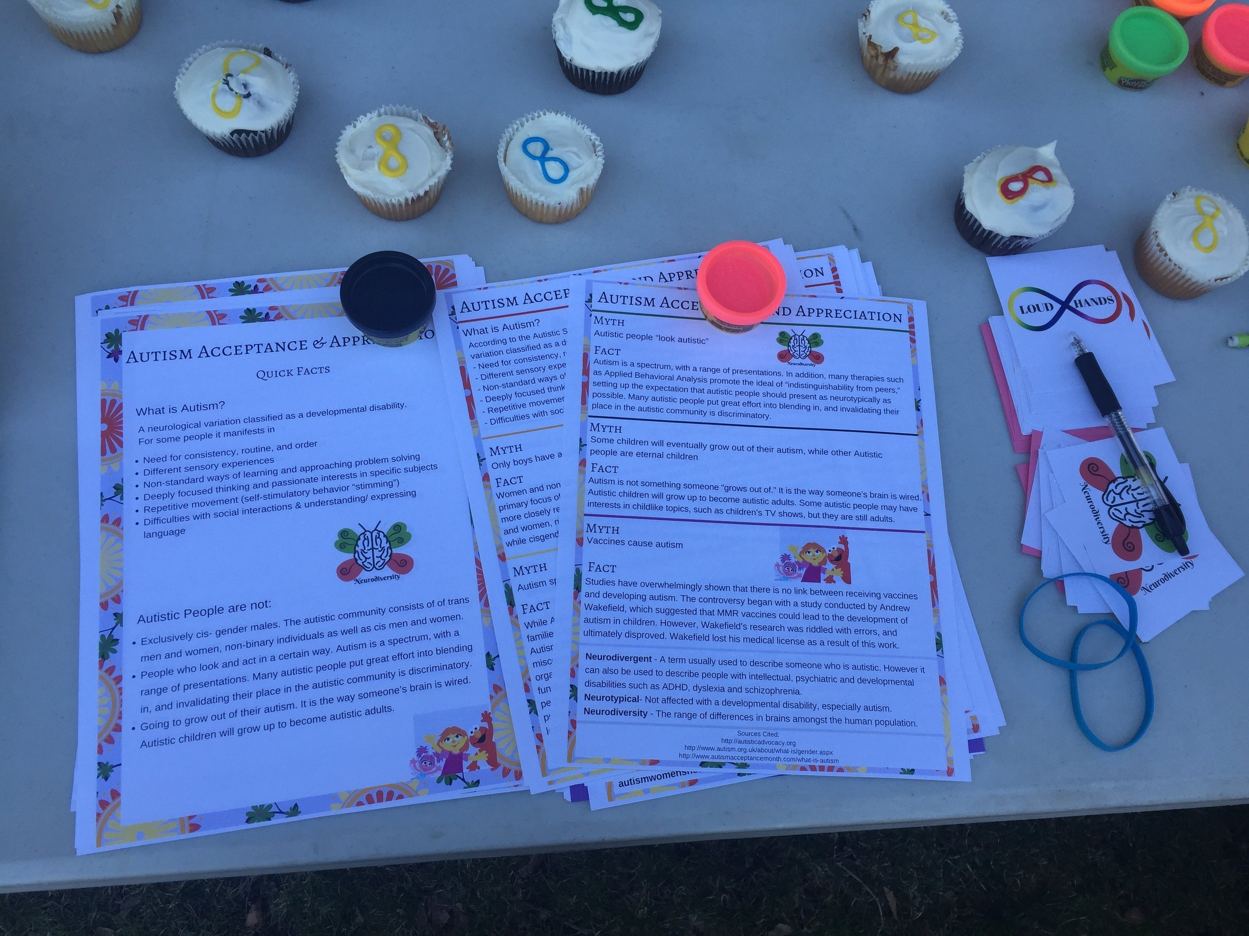 Image description:: Close up view of autism acceptance flyers, cupcakes with colorful infinity symbols on white frosting and mini tins of Play-do