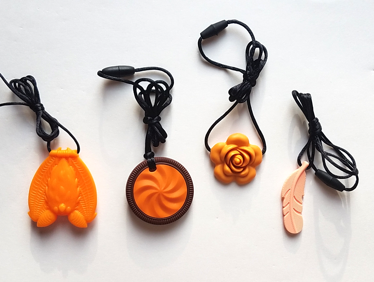 From top left: Orange bat, orange cookie, mango blossom, peach feather.
