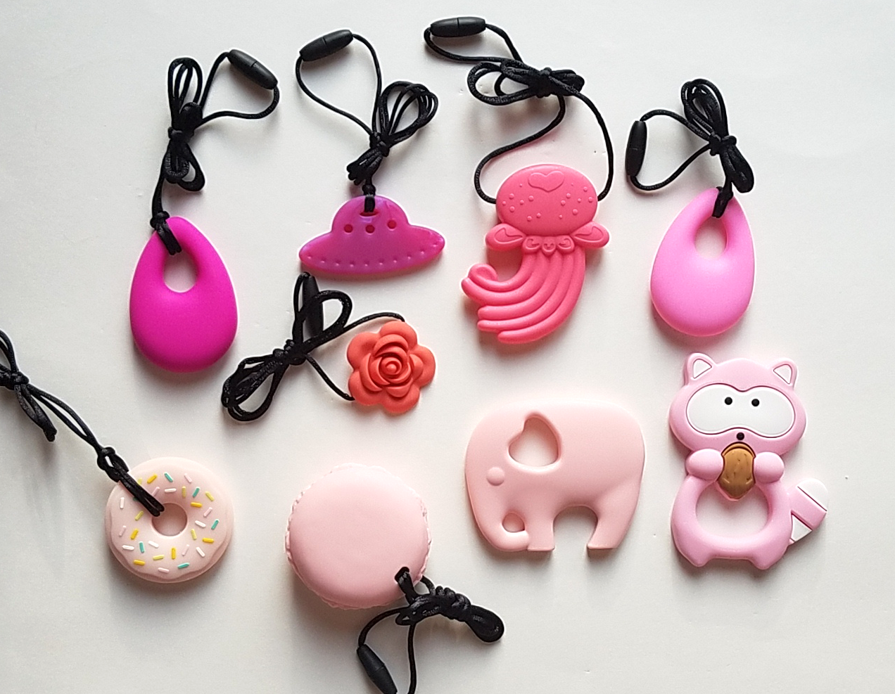 Clockwise from top left: Fuschia droplet, ruby UFO, pink jellyfish, pink droplet, pink raccoon, pink elephant, pink macaron, pink donut, coral blossom.