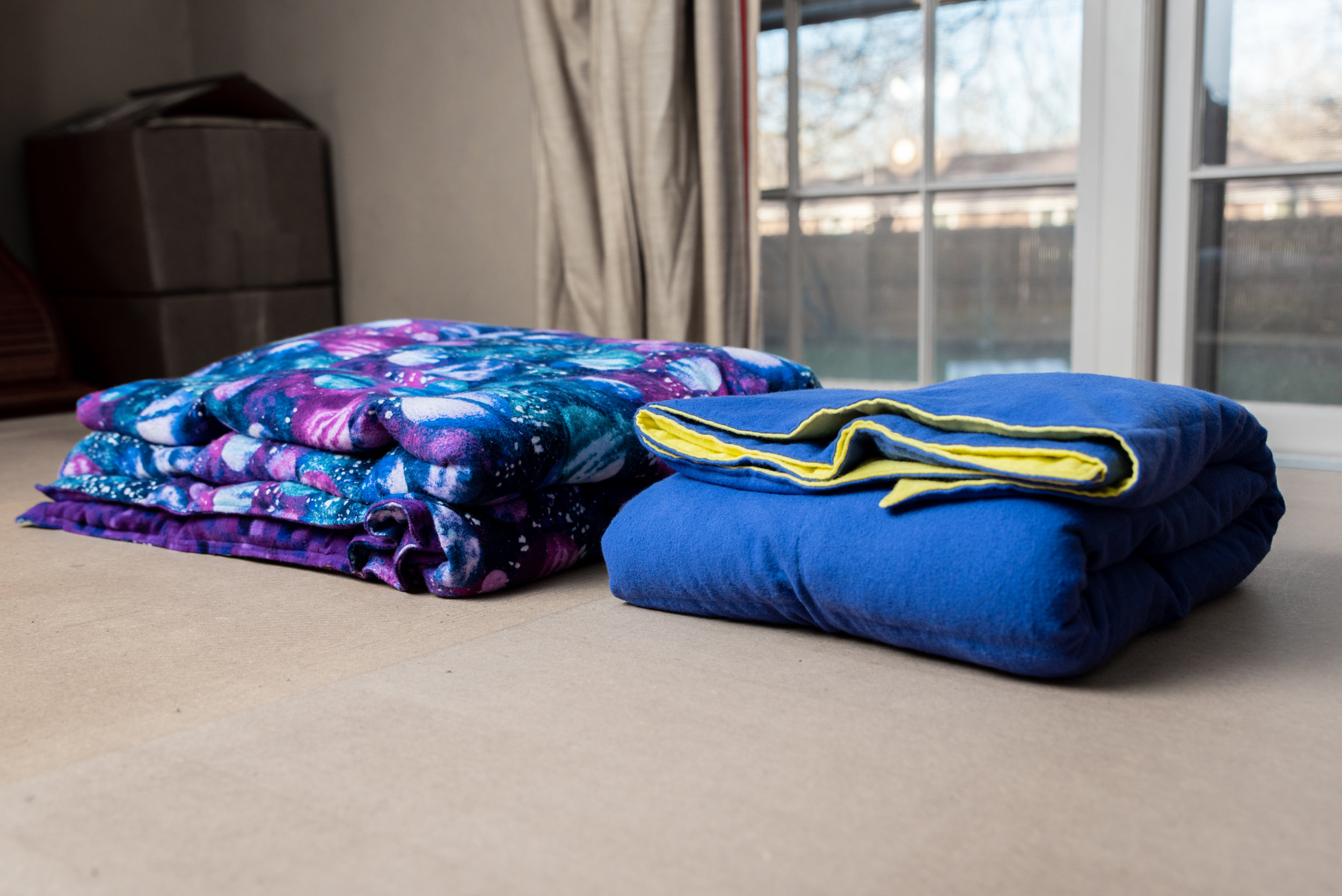 Two weighted blankets folded side by side on a bed. The one on the left has a fabric pattern of deep blues, purples and white and the one on the right is two toned, with blue on the outer side and yellow on the side that is folded inward.