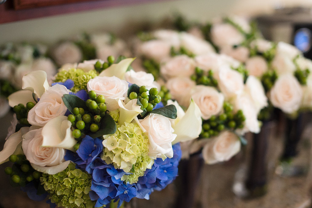"""Here are the bridesmaid bouquets and bridal bouquet. We stuck with simple white roses with green hypericum for the bridesmaids bouquets so they would really show against the dark navy dresses, and for the bride's bouquet we gave her """"something blue"""" by adding the blue dutch hydrangea and white calla lilies, a symbol of beauty."""