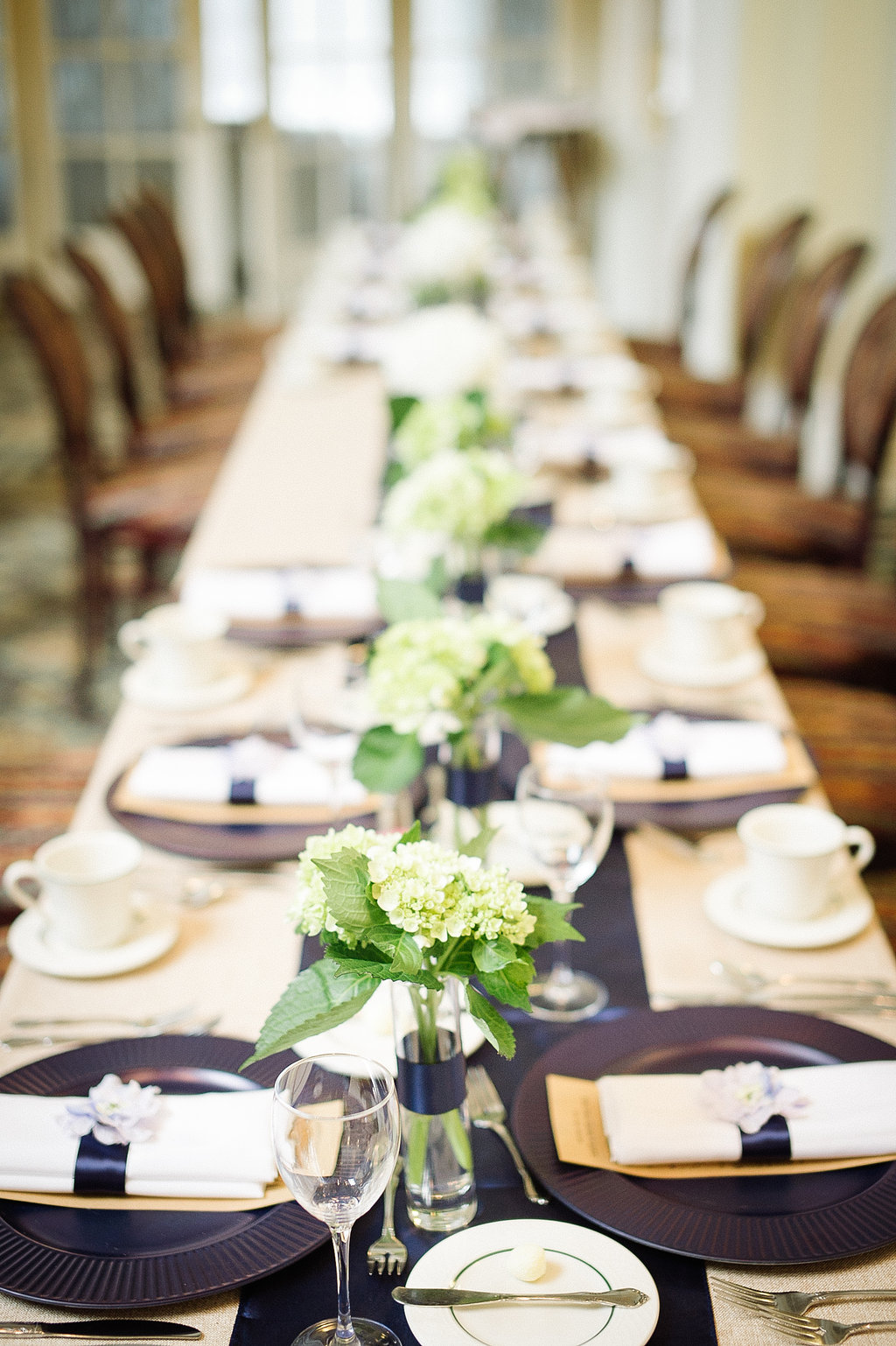 For this wedding the bride and groom did a modified head table, so we did small cylinder bud vases with a stripe of satin navy ribbon filled with small bouquets of green and white hydrangea over a matching navy satin runner.