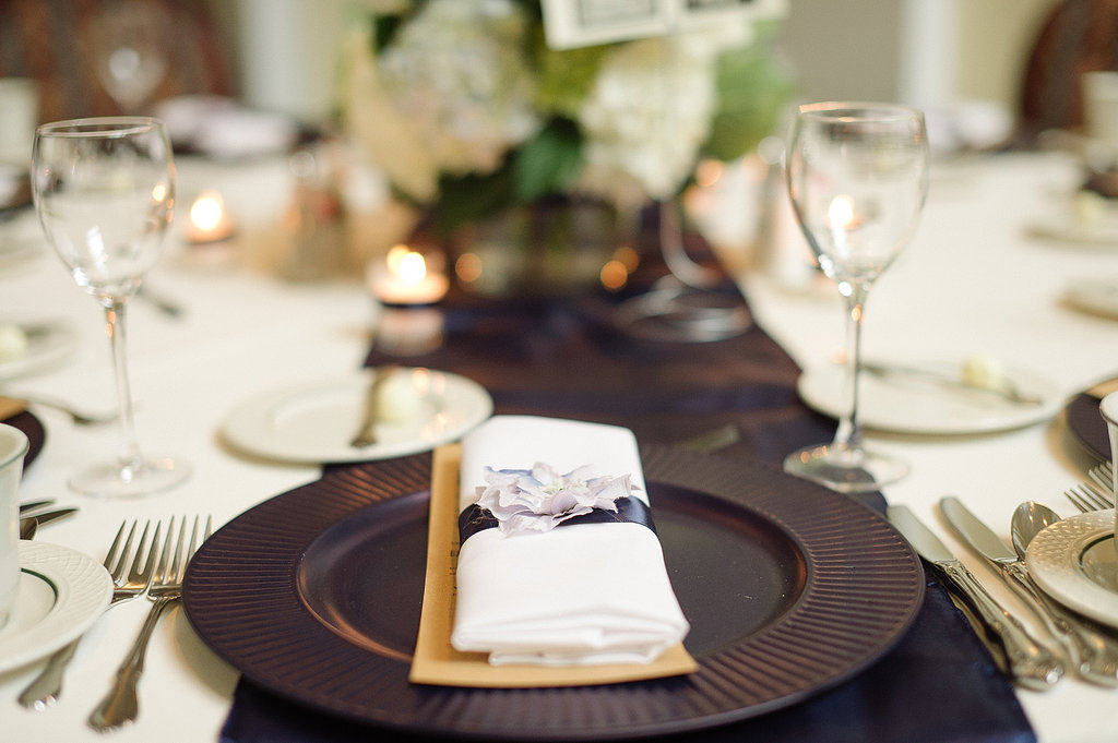 For the place settings we did a navy blue charger with long folded white napkins tied with a navy stripe of ribbon and a pale blue blossom to soften the intensity of the preppy lines.