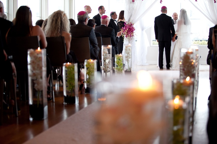 We did a simple white aisle runner for the bride and lined it with tall square vases with submerged cymbidium orchids in whtie and green over river rocks topped with a floating candle to create simple elegant pieces to line the aisles with.  ***We also transfered the large white cymbidium Vases to the Reception Room as a second type of centerpiece I love being able to use elements from the ceremony in the reception, it is a great way to get a lot of use out of your flowers when you do everything in one venue