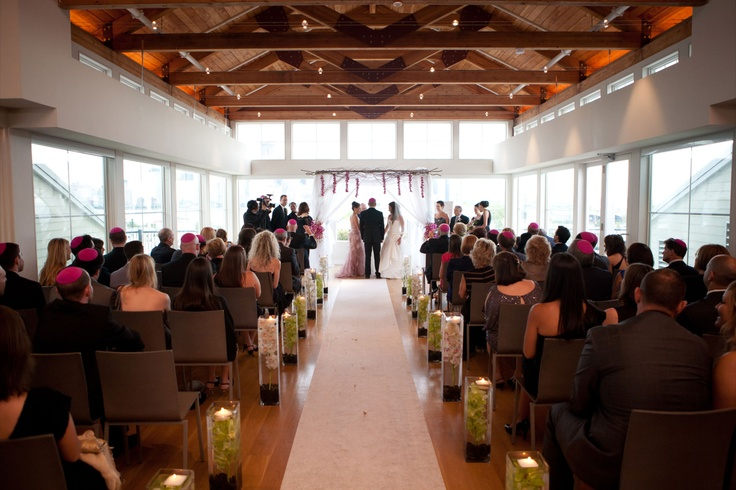 The ceremony was held on the top floor of the venue, a very large room with exposed beams, white walls and lots of windows. We created a structured Chuppa and draped it with sheer white fabric to allow the light from the windows in. The decor was a simple branch design to pull in a natural look with hanging purple dendrobian orchids to add a pop of color to the piece.