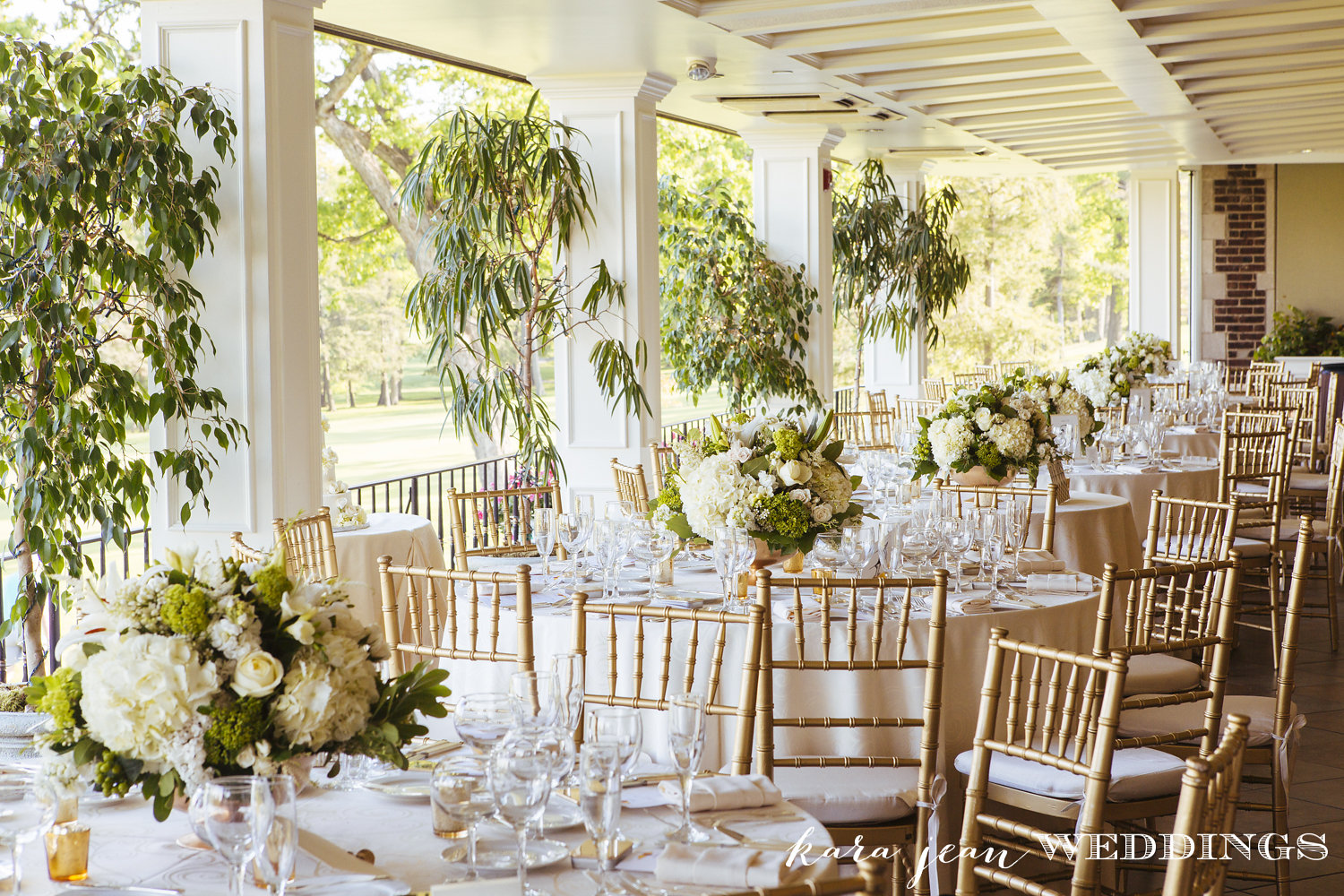 Reception room shot, bringing the outdoors in with large overflowing centerpieces of white and green flowers.