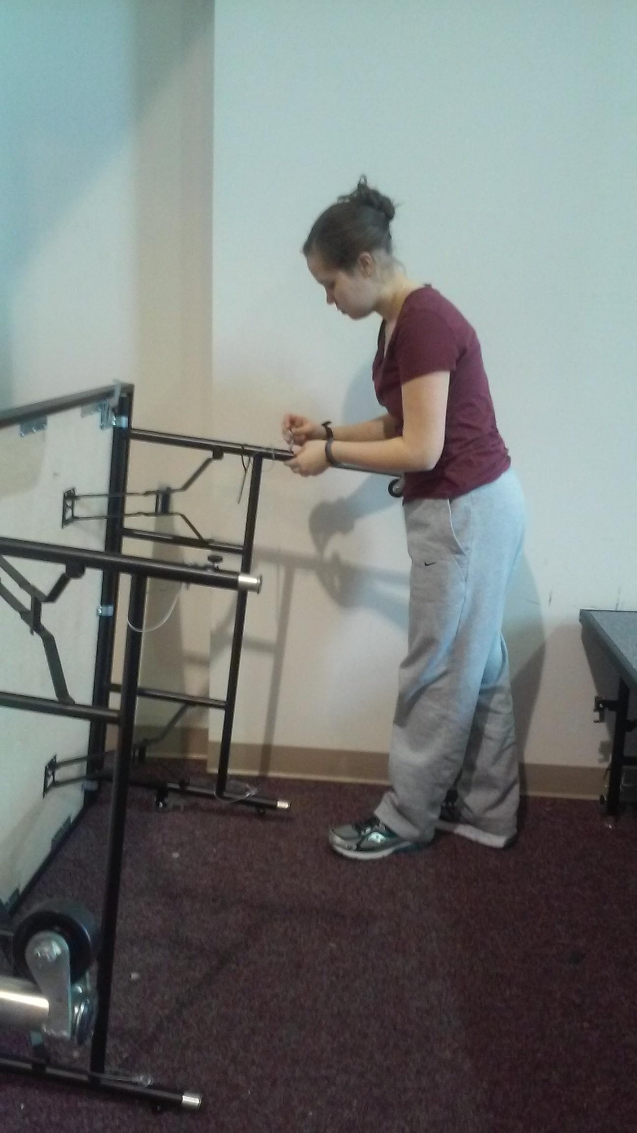 Elizabeth Neumann working on raising the stages.