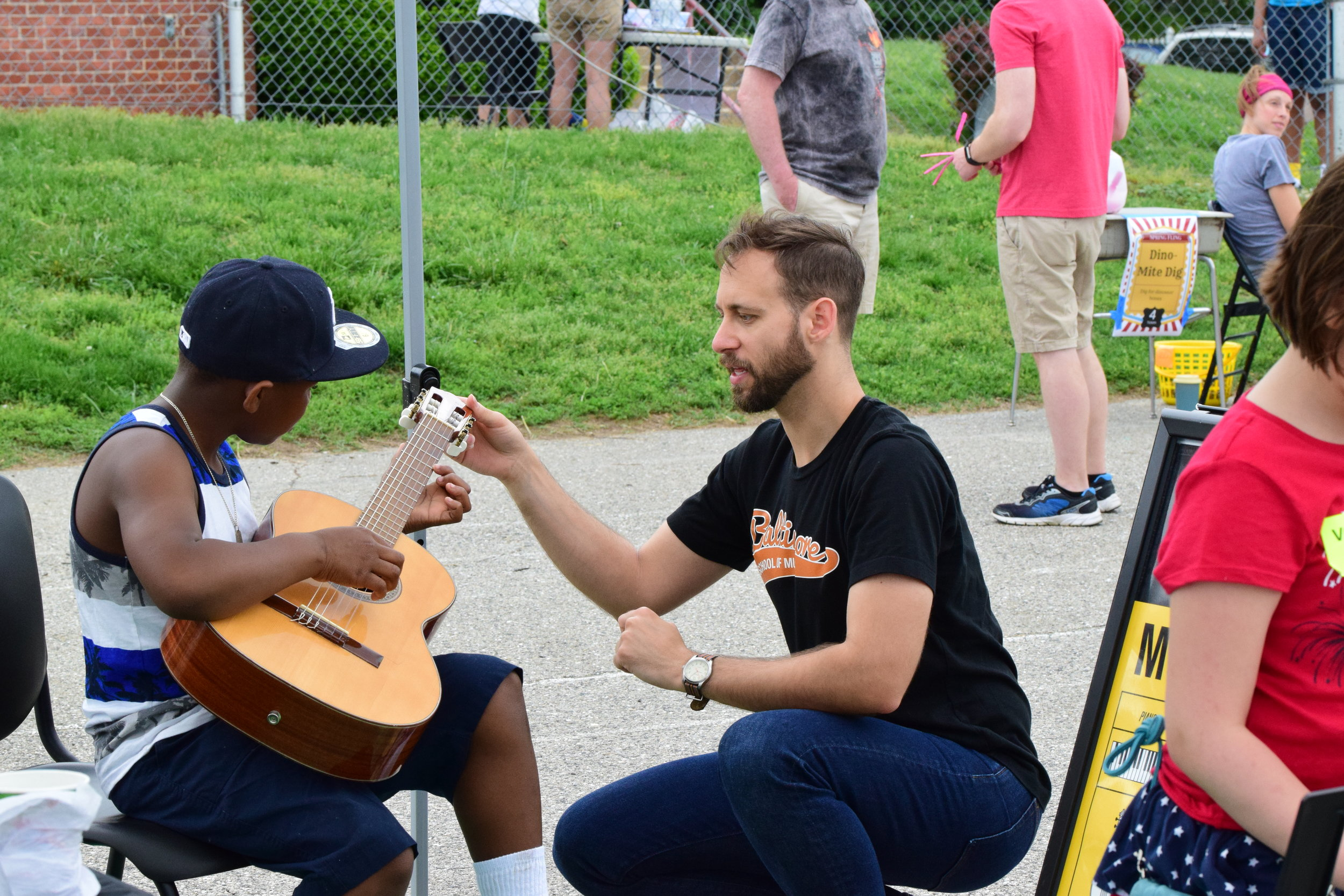 Teaching how to hold and play the guitar at an event in Baltimore City.