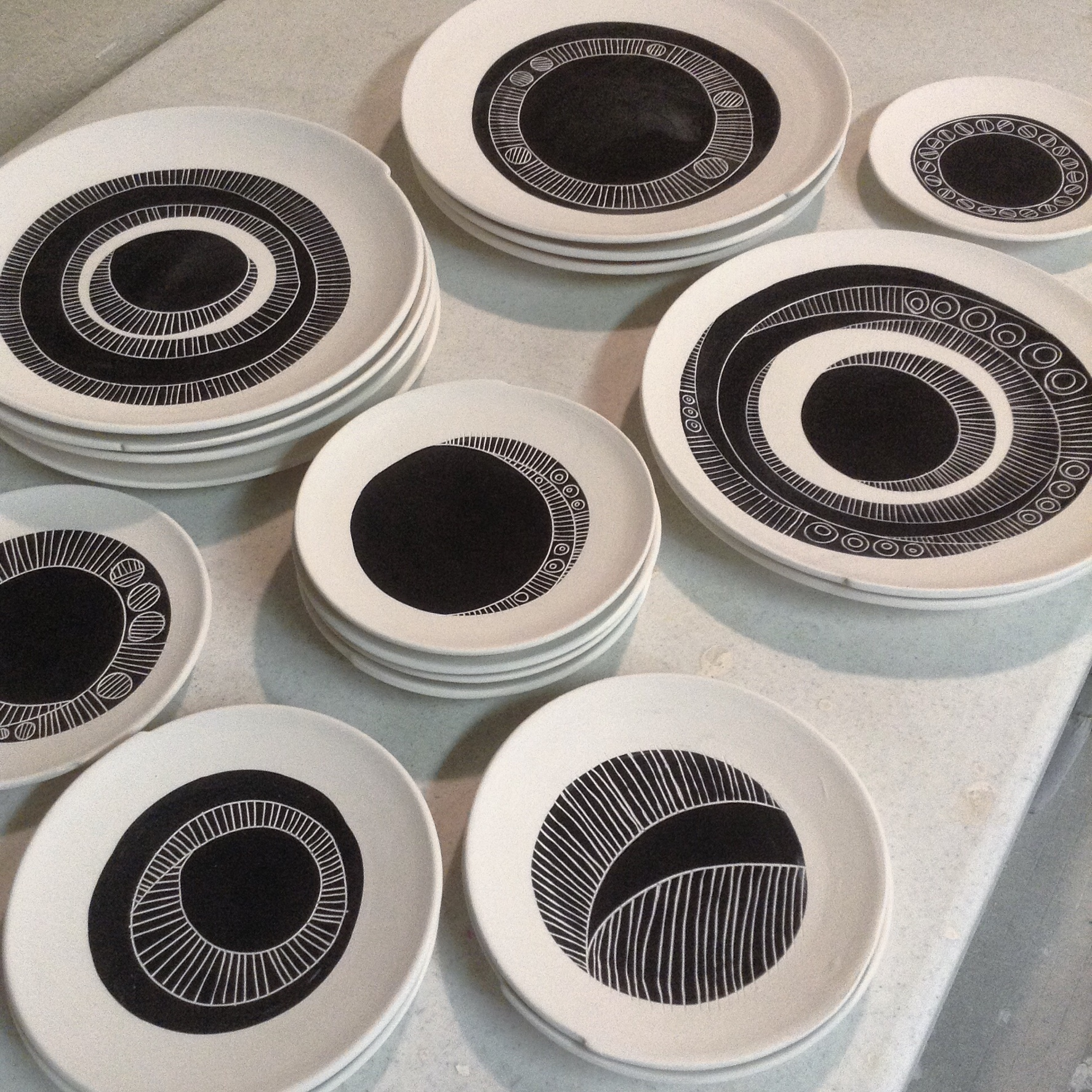 Ready for glazing: porcelain wheel thrown plates with sgraffito designs.