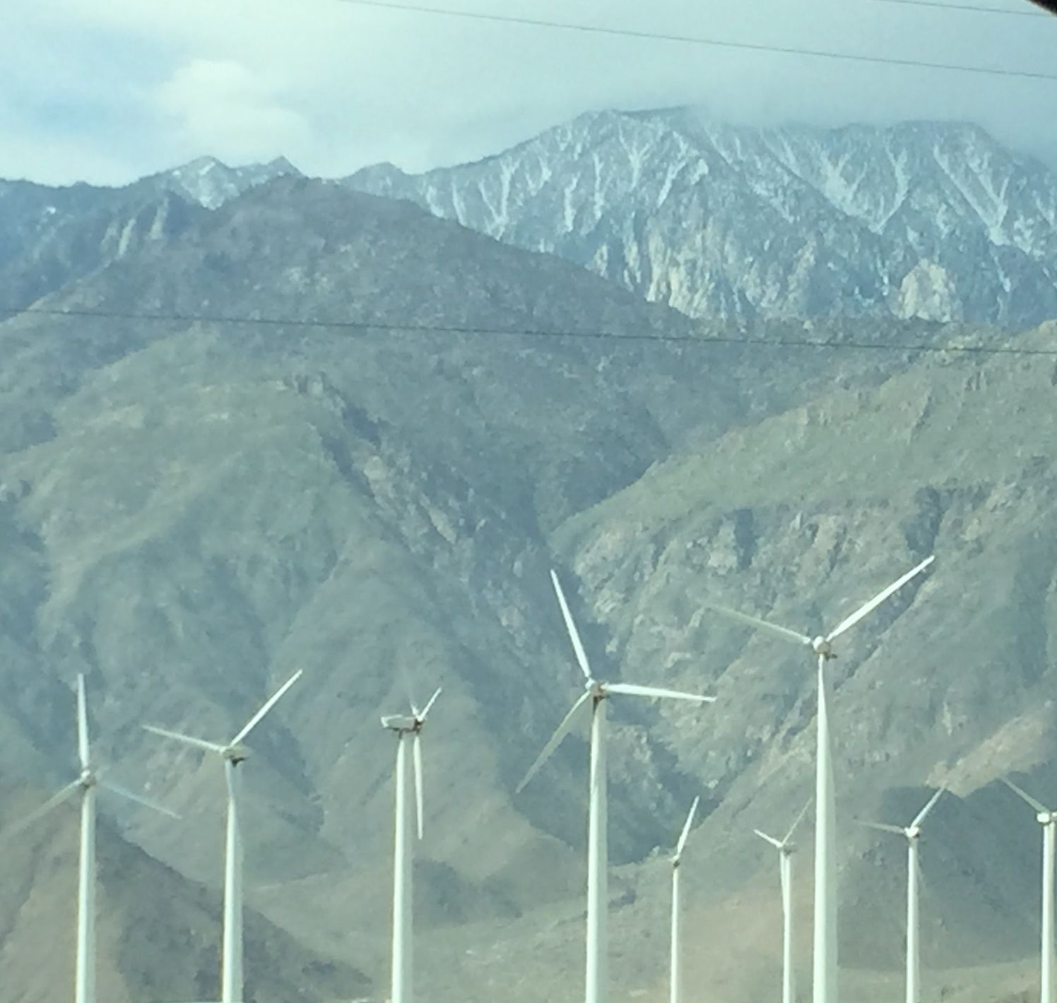 Windmills in the Palms Springs area with the San Jacinto Mountains peaking out with sparse snow.