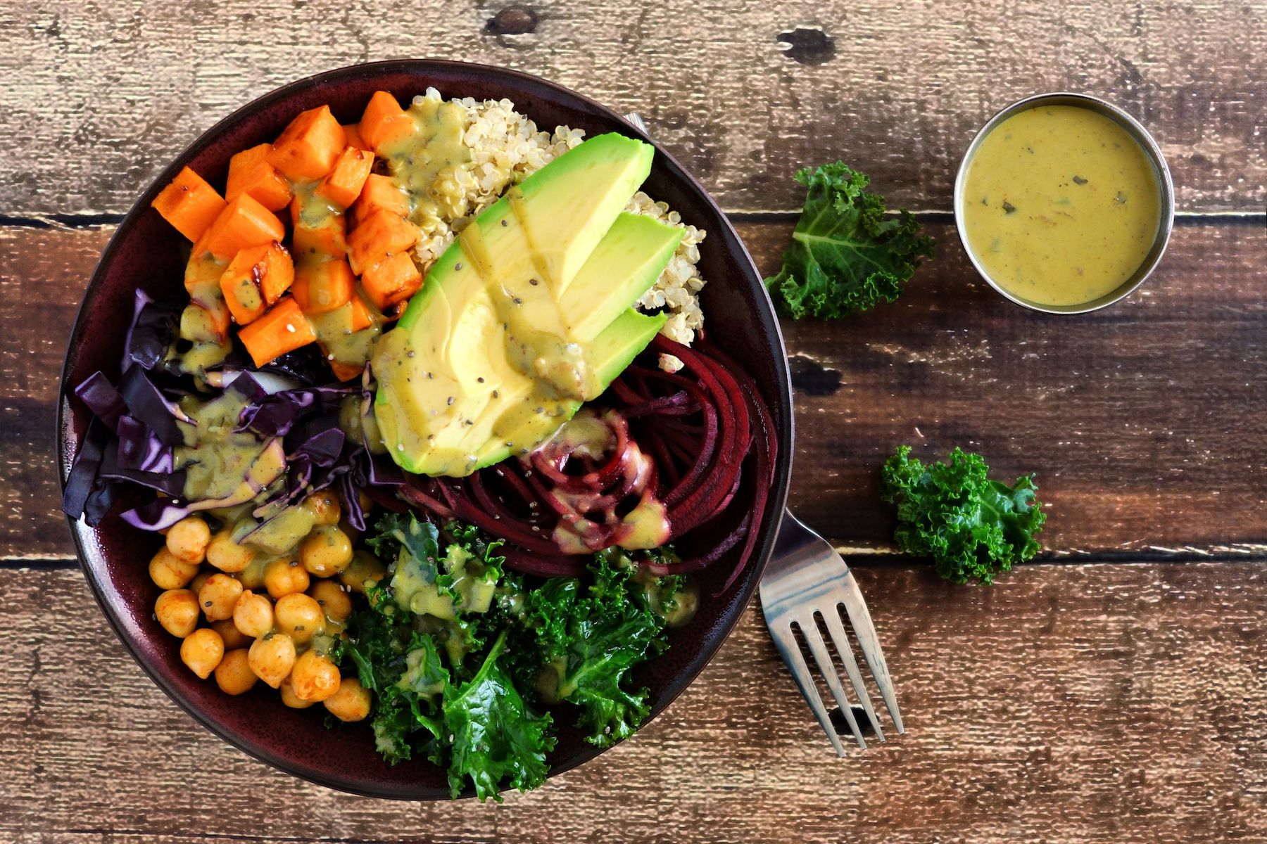Buddha bowl with quinoa, avocado, chickpeas, vegetables on a wood background, Healthy food concept. Top view.