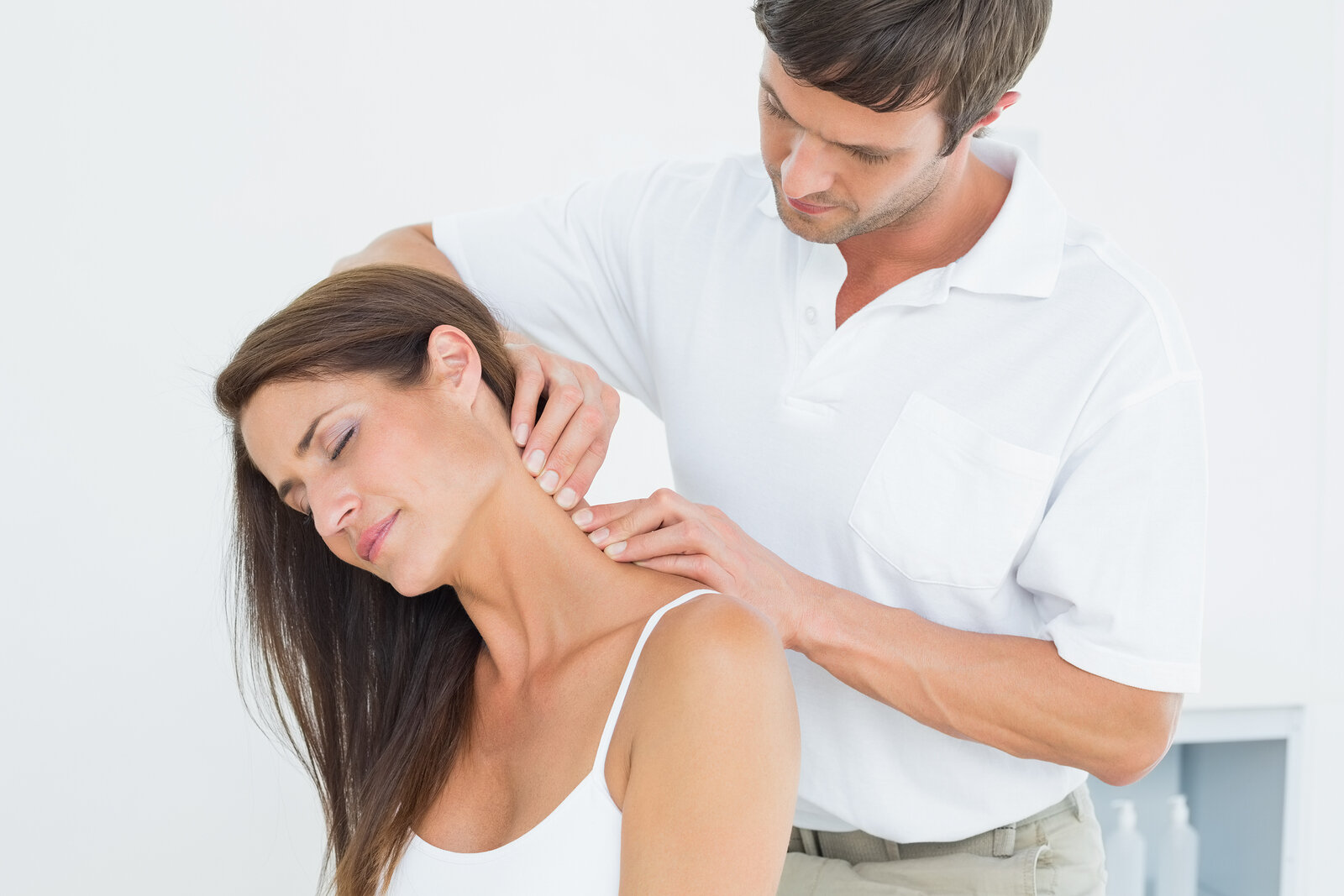 Male chiropractor massaging a young woman's neck in the medical