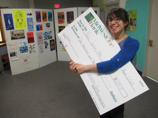 Kalmia holding a large check in the future IC Press Coop space (April 2013)