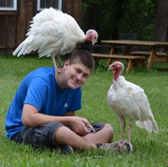 Jake Clements with two white turkeys in a field.