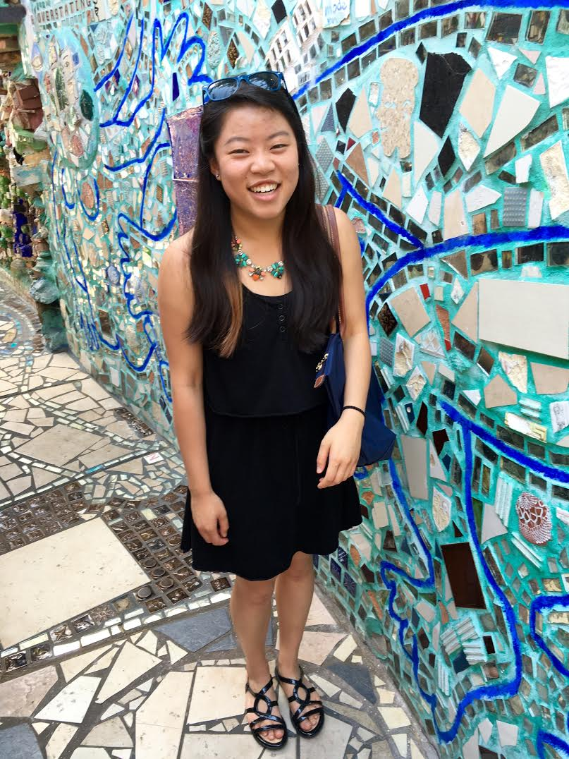 Picture of Nicole Moy in front of a mosaic.