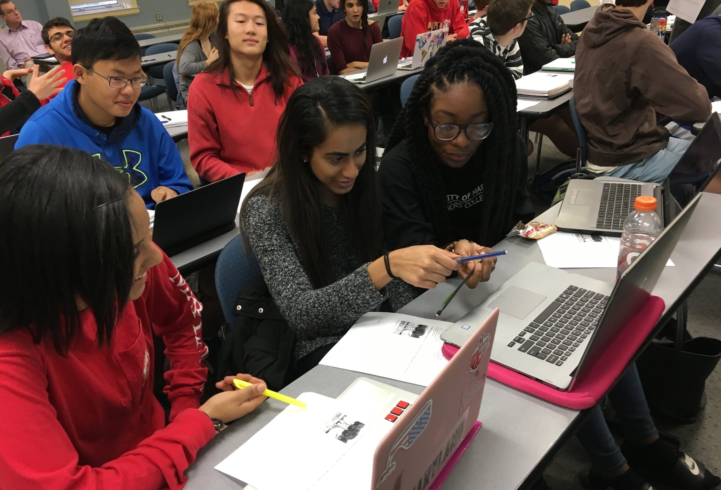 ILS students with laptops working together on a project