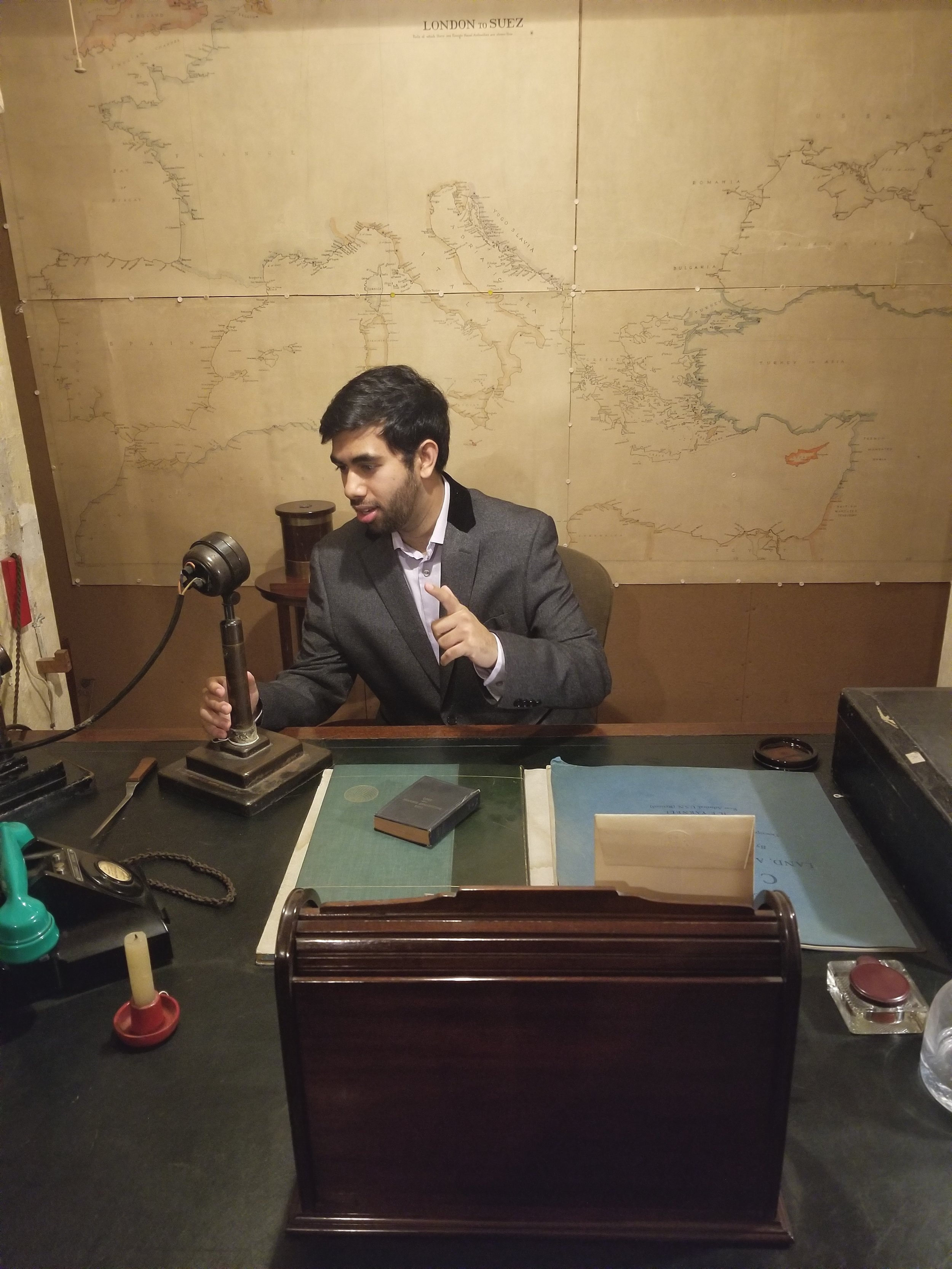 England - Yousuf Khan, class of 2018, from Winston Churchill's desk where he addressed the nation during WWII. Yousuf is at the University of Cambridge earning a Master's of Philosophy in Pathology.