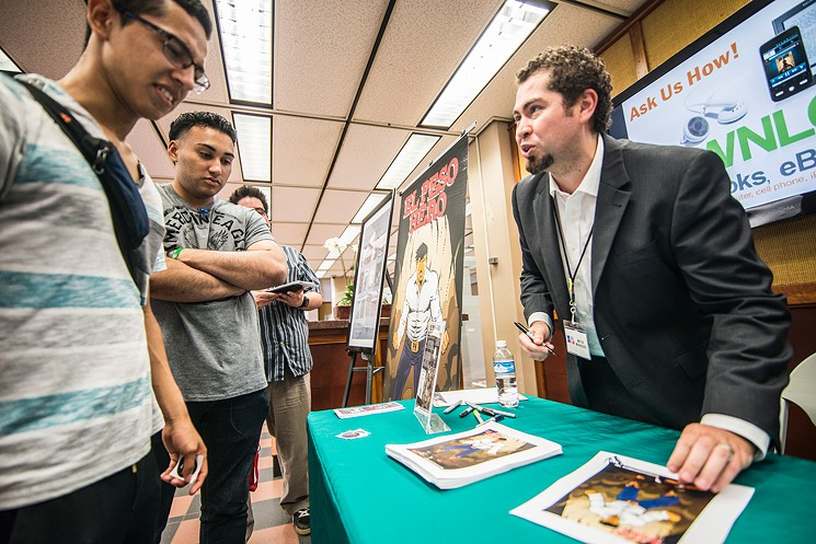 Comic book artist Hector Rodriguez talks with UT Dallas students at welcome week book signing. Photo by: Can Turkyilmaz