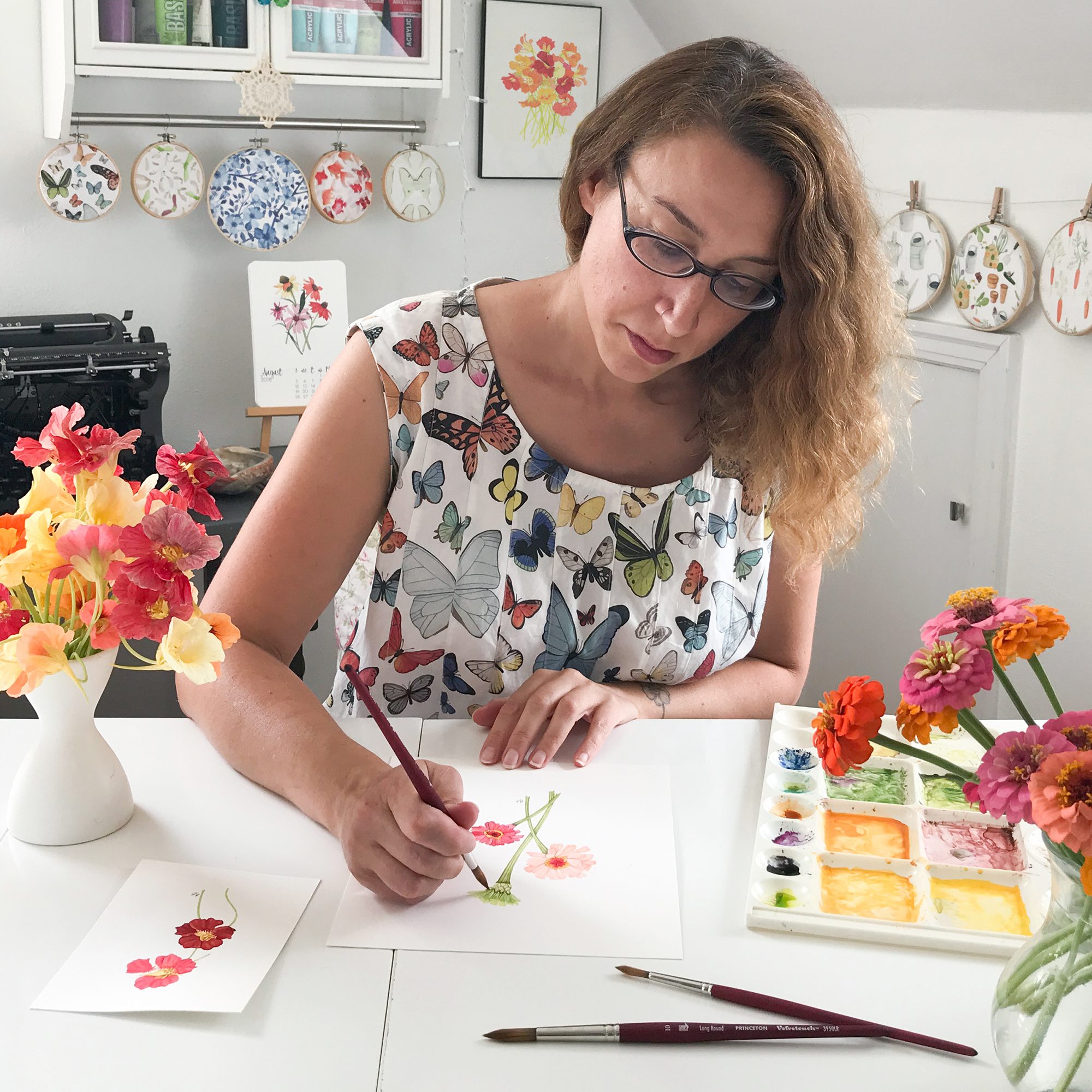 Anne Butera Painting In Her Studio in the Summer Surrounded by Flowers and Wearing her Butterfly Fabric