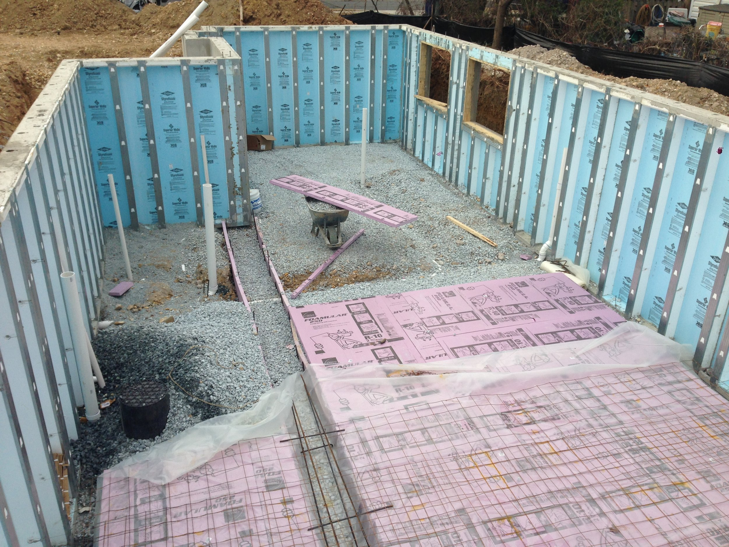 On schedule with the foundation. The pink and blue stuff is rigid insulation that will provide the floor with a nice consistent temperature throughout the year.