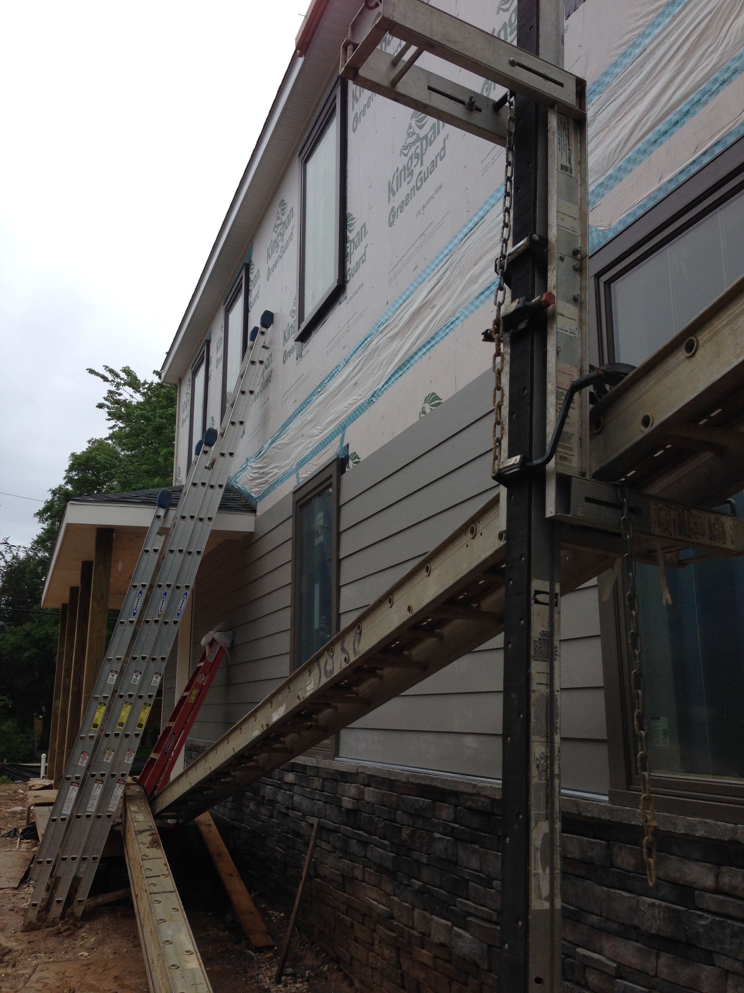 Siding continuing to go up and wrapping around the front.
