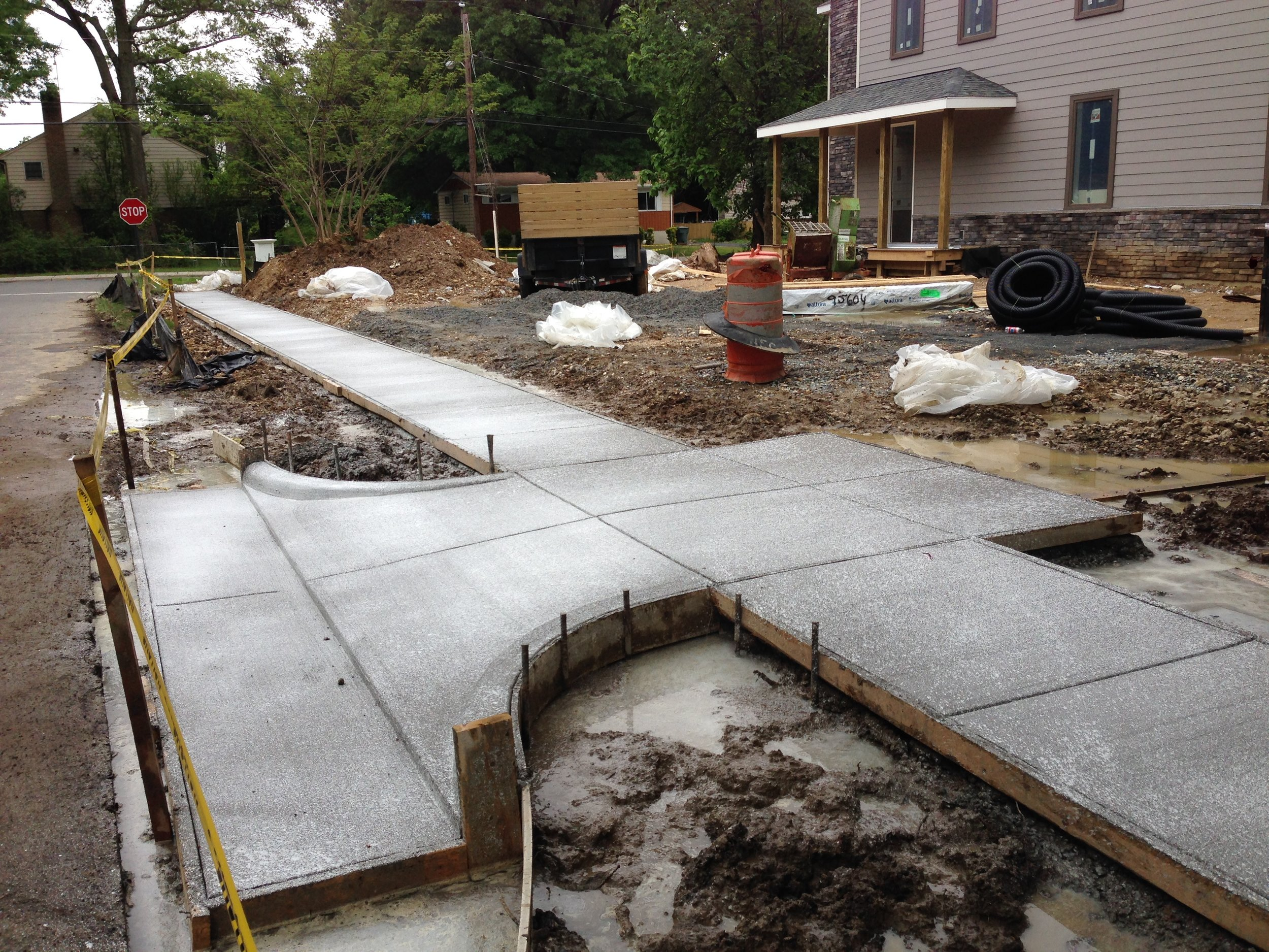 Concrete pour complete. Sidewalk and driveway installed! The entrance to the driveway is so small because we wanted to avoid the roots of the nearby Oak tree.