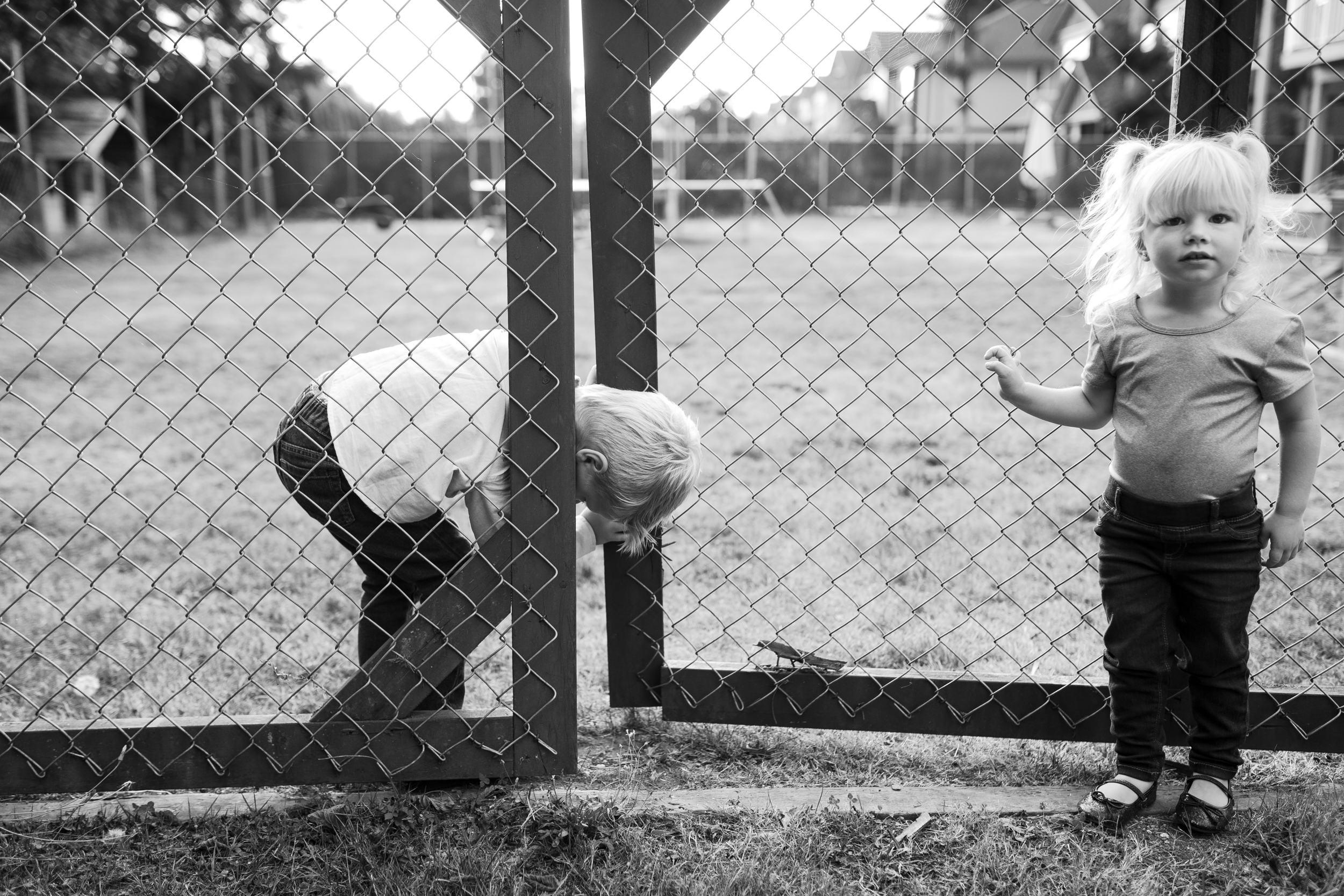 kids trying to squeeze through a gate