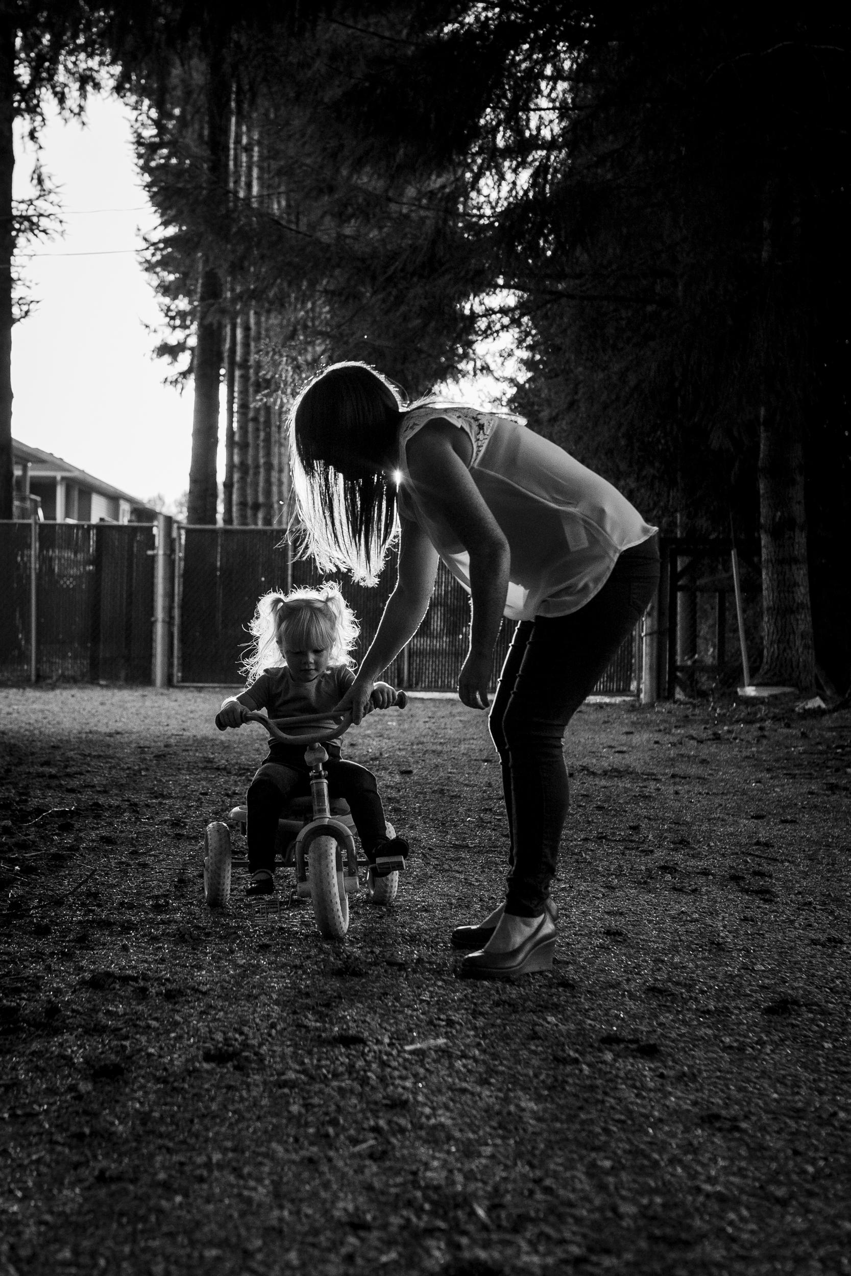 backlit mom helping daughter on bike