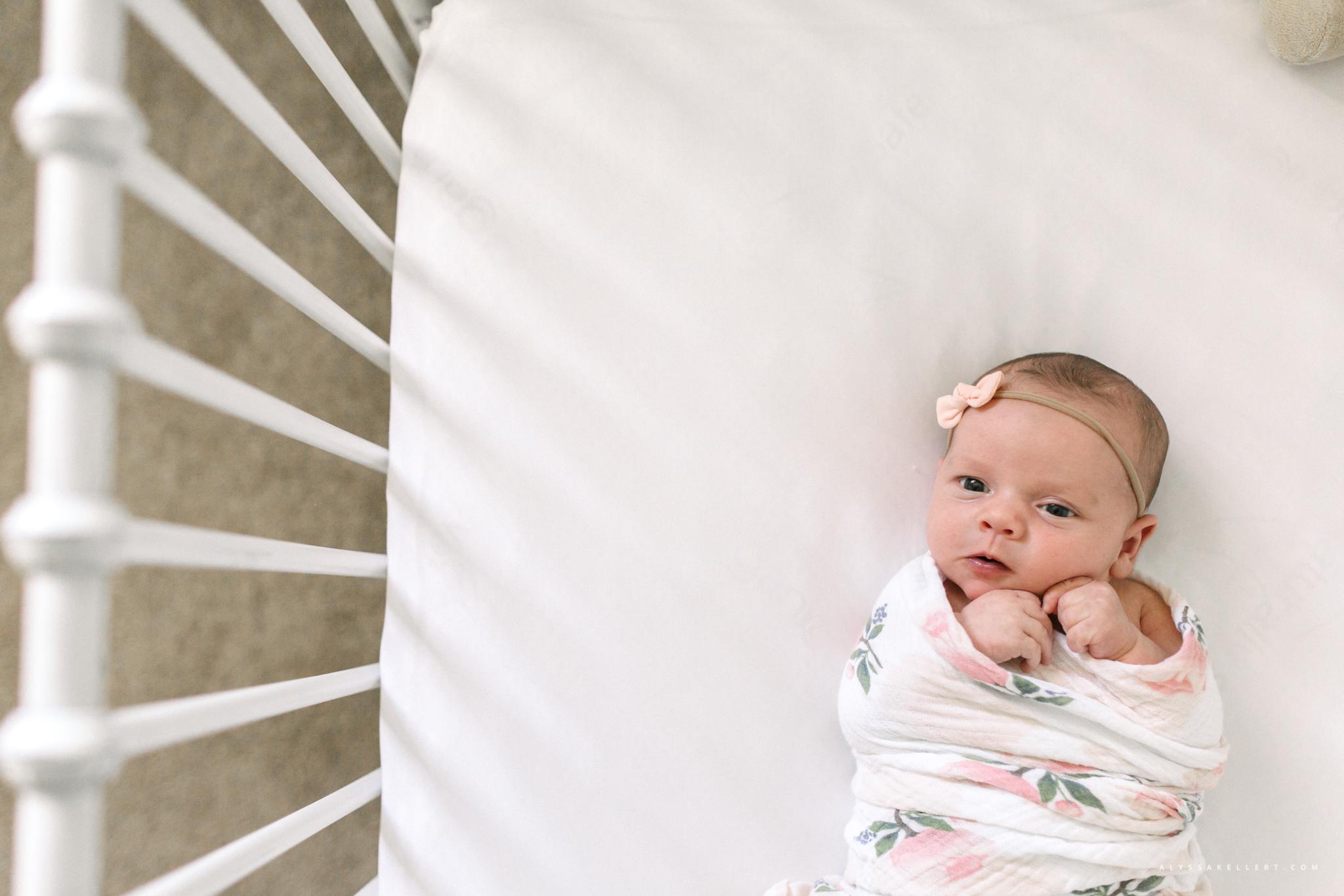 baby girl lying in crib during newborn photo session