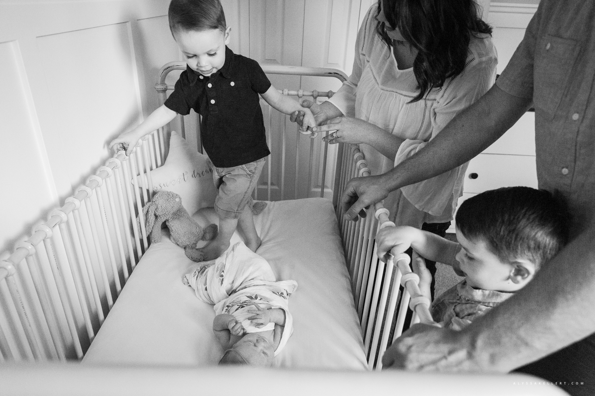 family reaching in to crib to see baby newborn girl during documentary session