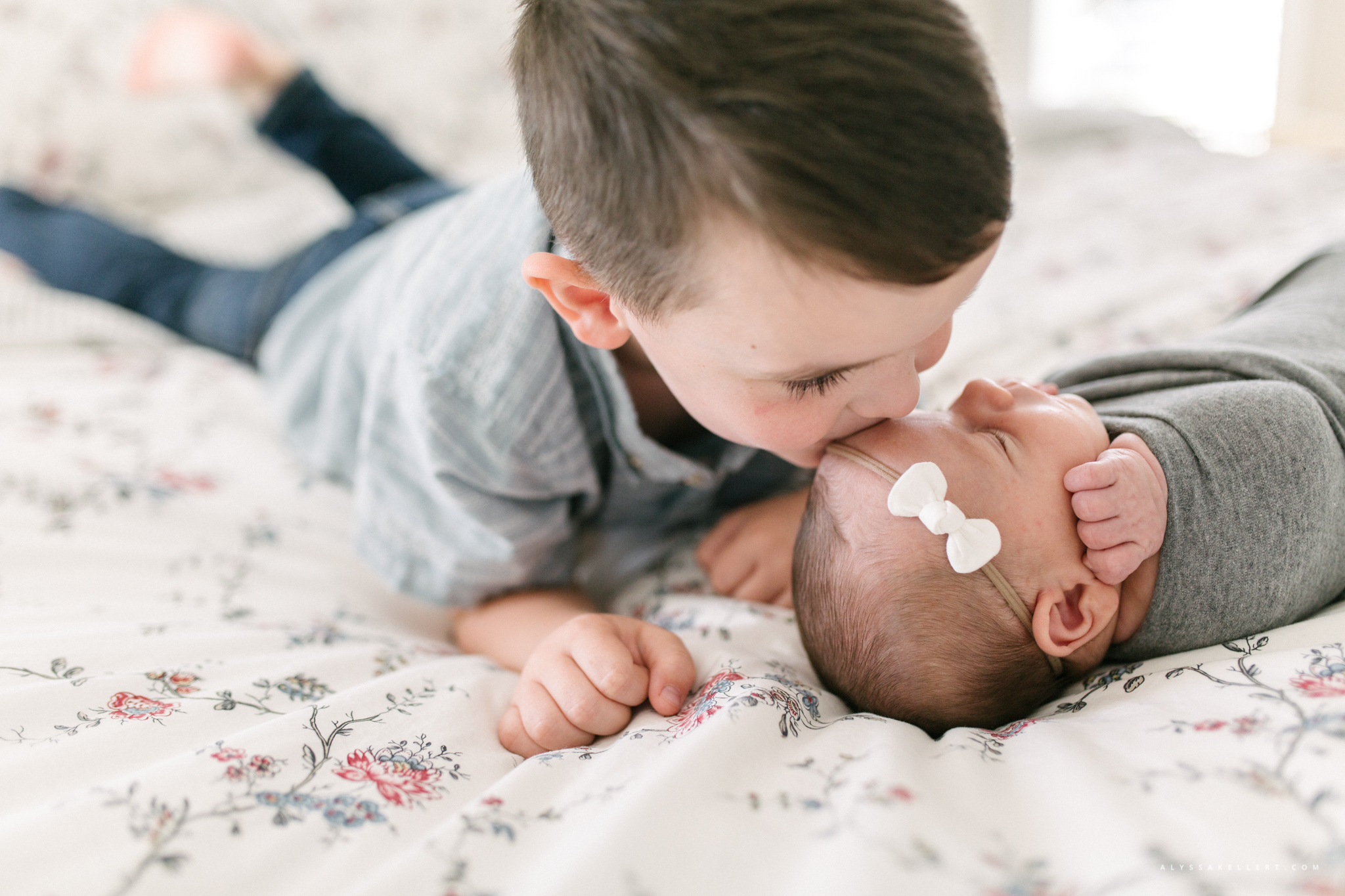 brother leaning over to kiss his baby sister on the head during lifestyle photo session vancouver