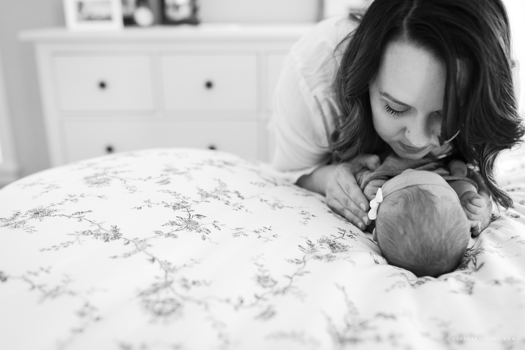 mom looking at her baby girl lying on the master bed during lifestyle photography session
