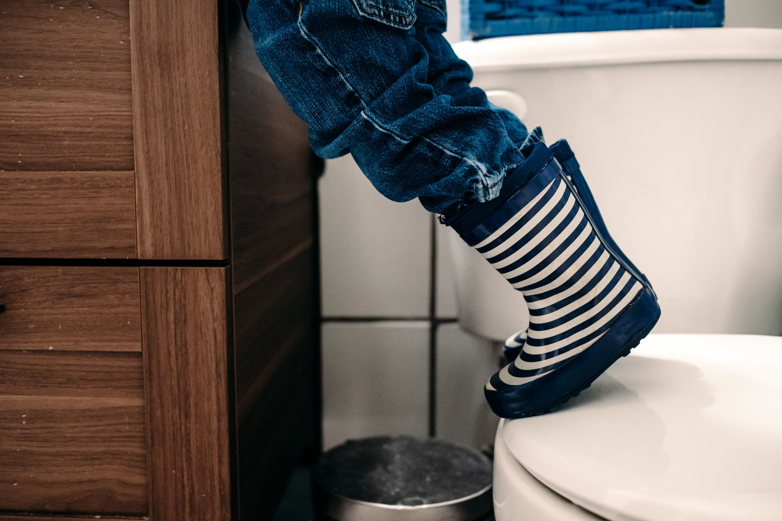 kid-standing-on-toilet-boots-rubber-toddler