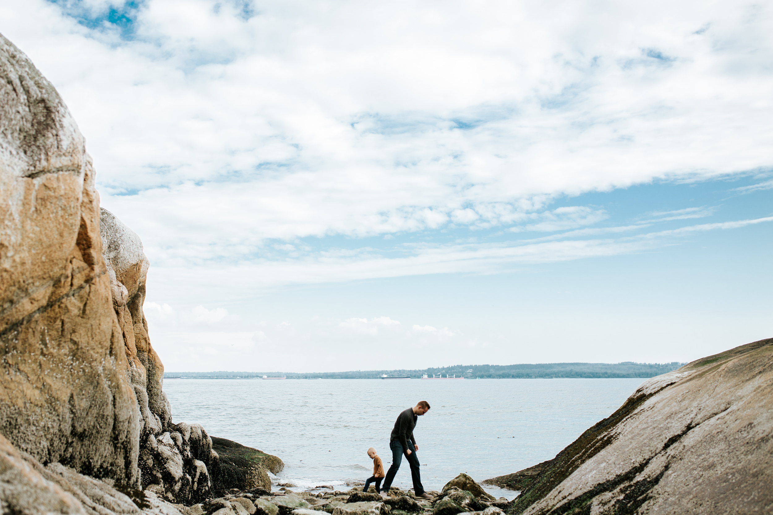 father and son walking near the ocean between rocks at lighthouse park with blue skies