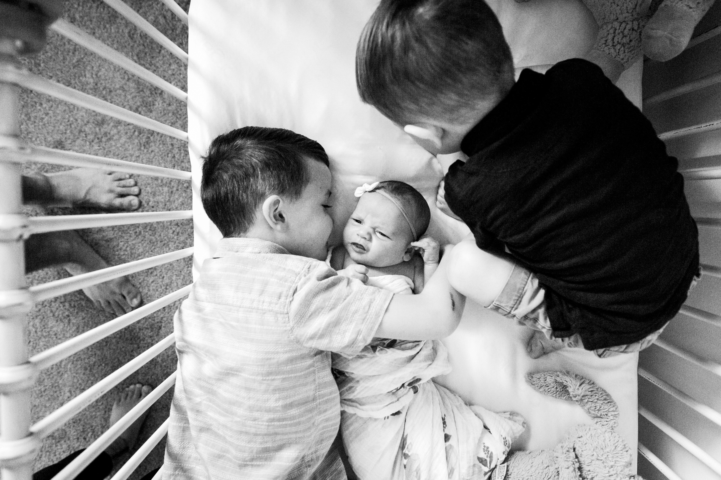 boys in crib with baby sister
