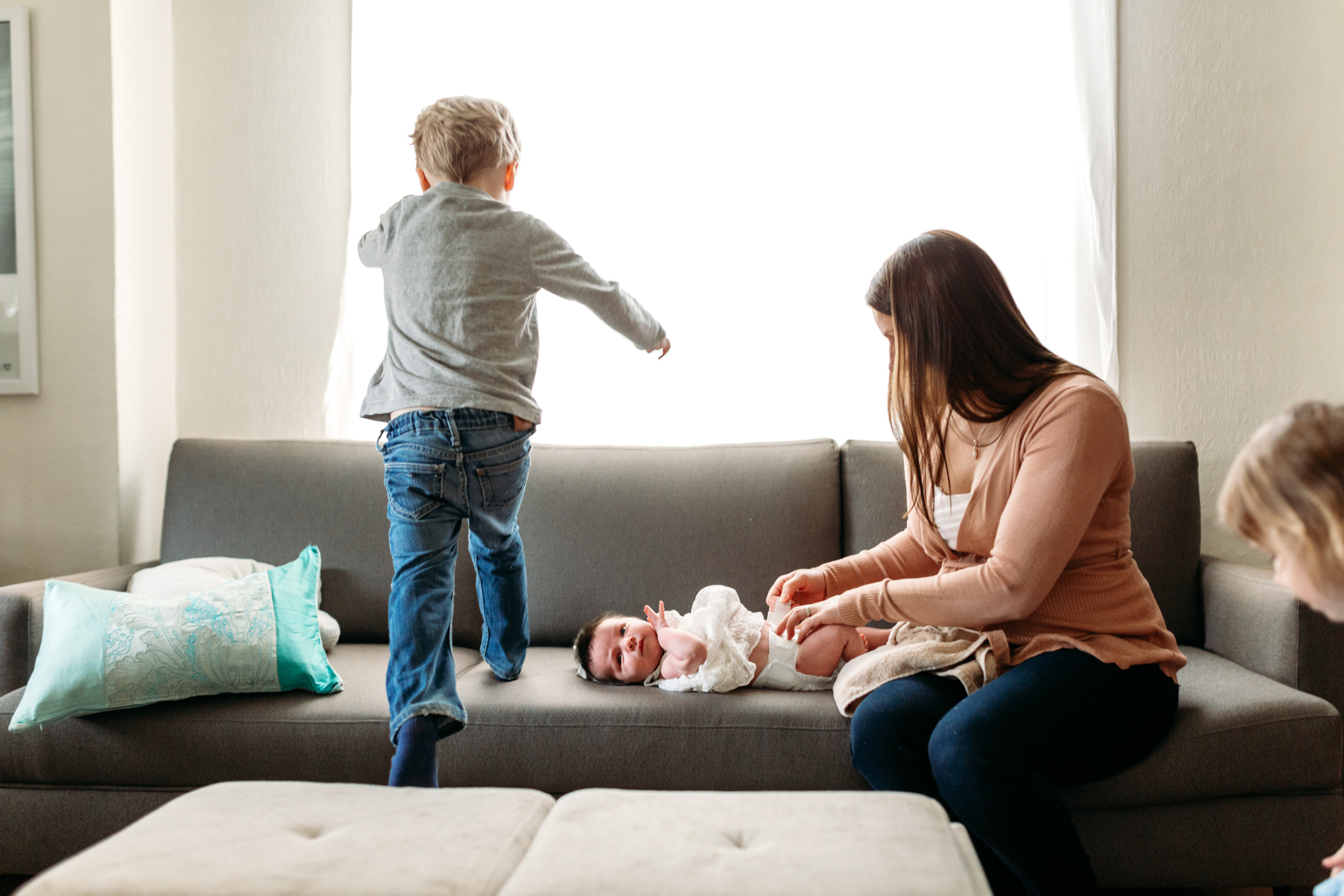 kid jumping on the couch nearly missing his baby sister