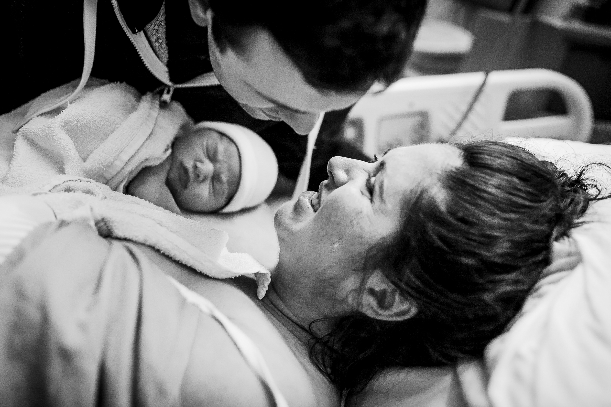 mom crying as dad comes in for a kiss after the birth of their first baby vancouver