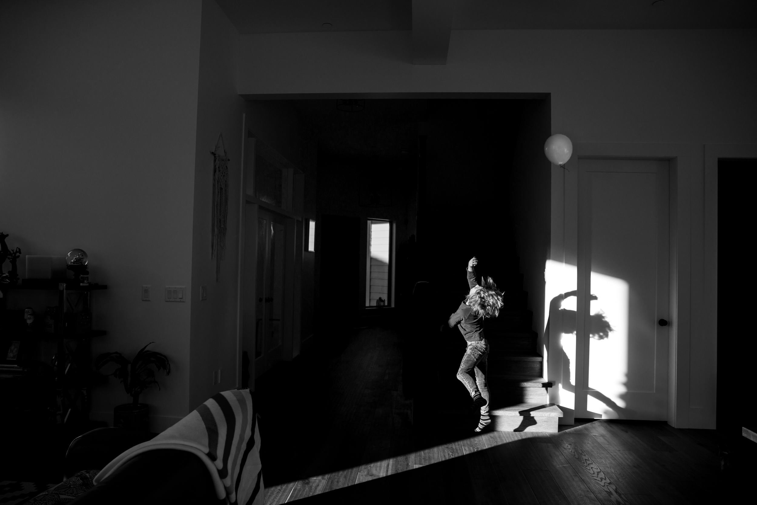 kid jumping to hit balloon in the shadows